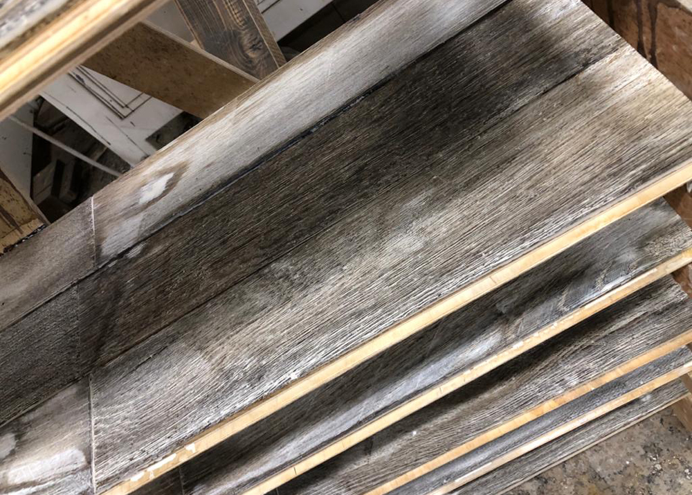 Whitewash reclaimed flooring in drying racks