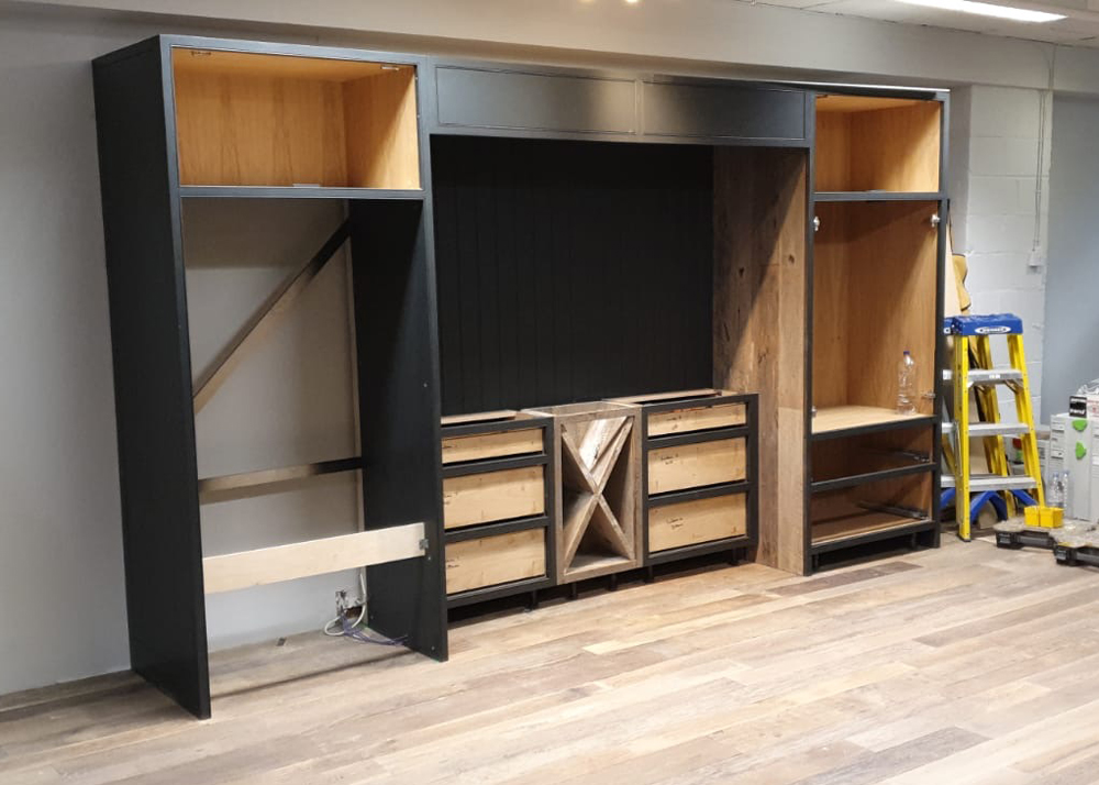 Tall painted bespoke kitchen units being installed in to London showroom