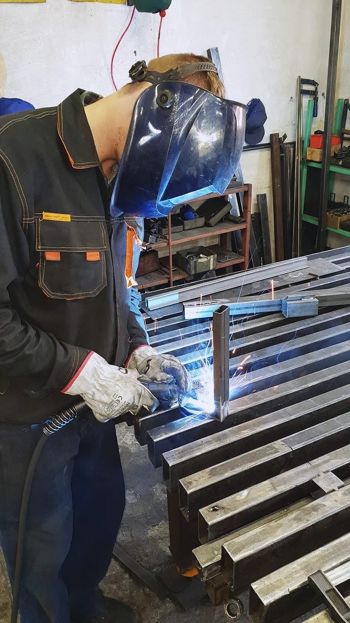 Worker welding hinges on to stock metal doors