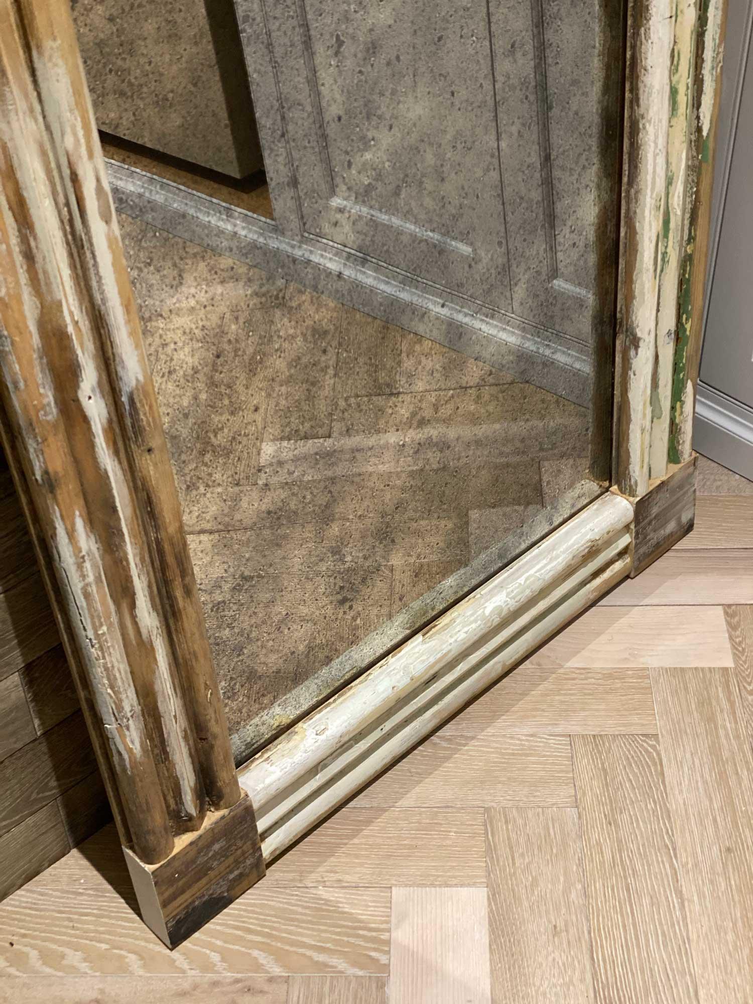 Antique mirror reflects parquet flooring