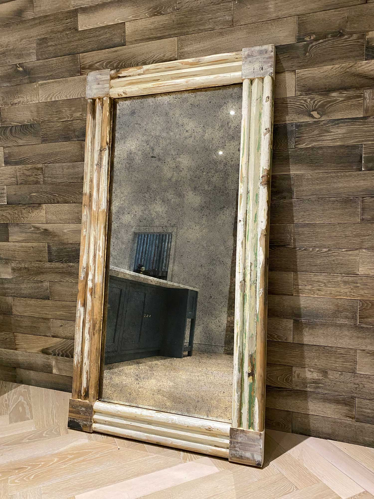 Large Antique mirror with reclaimed frame against parquet wall