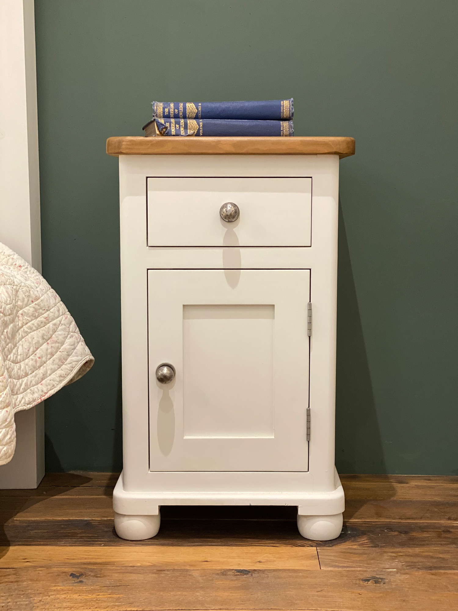 Painted round end bedside table with one door and one drawer against green wall