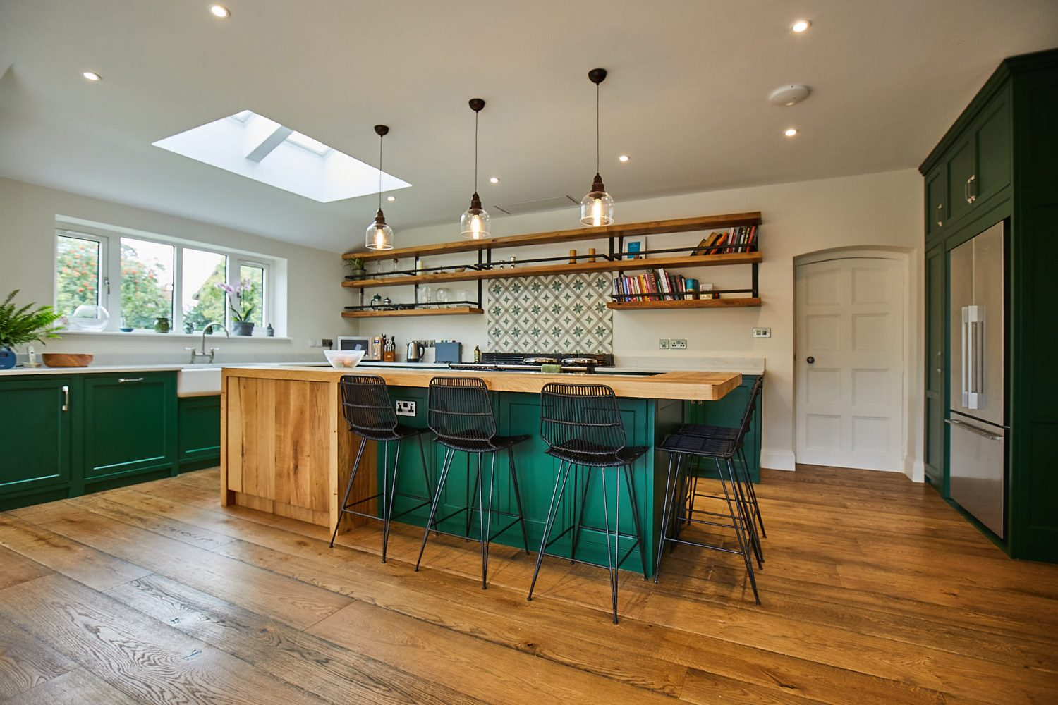 Bepoke kitchen island with clean oak cabinets contrasting with green painted cabinets