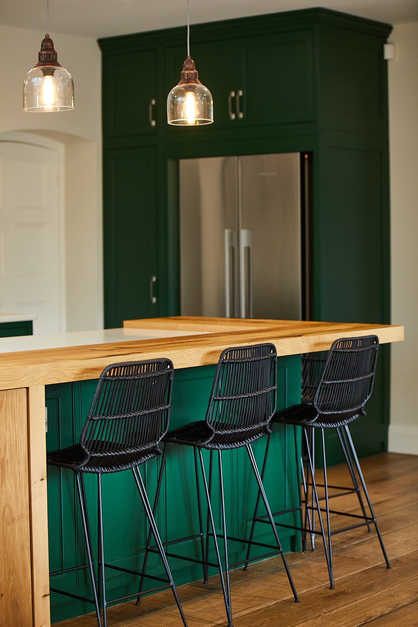 Black bar stools sit under green kitchen island with glass pendant lights above