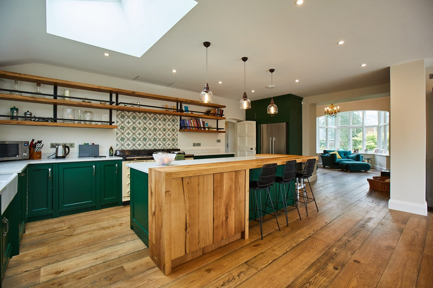 Large green kitchen with floating oak shelves and oak breakfast bar