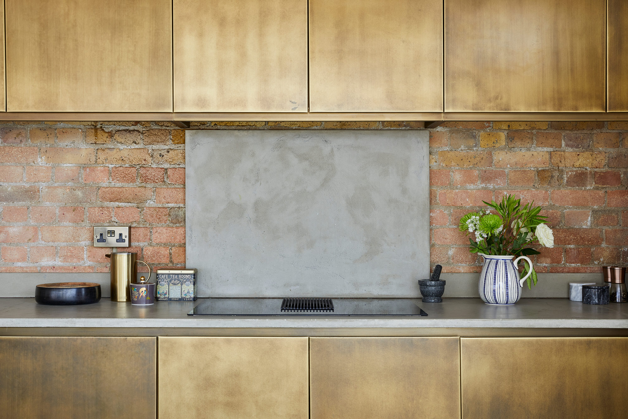 Brass metal kitchen cabinets with concrete countertops and backsplash