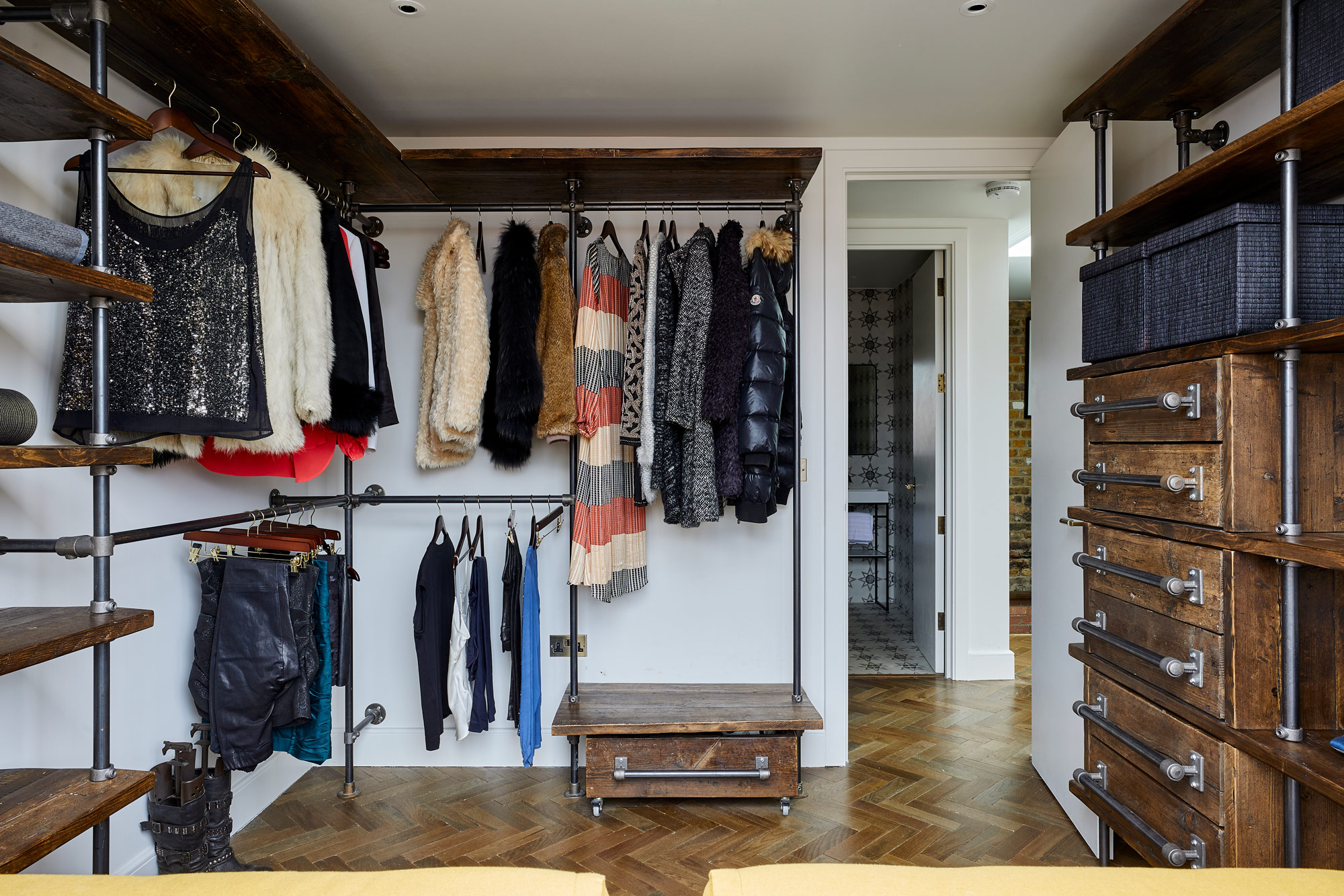 Open plan walk in wardrobe with rustic shelves and pipework
