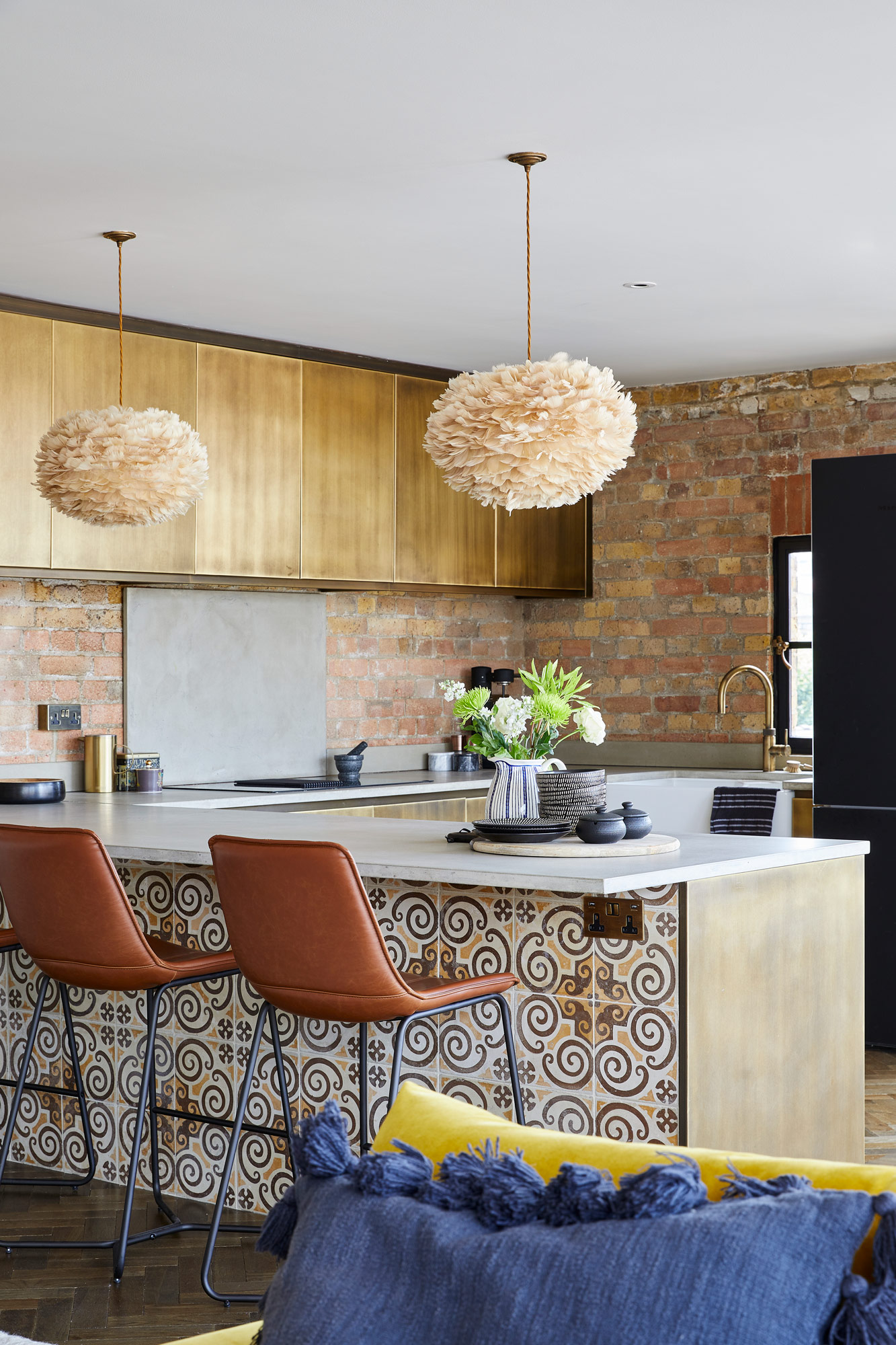 Reclaimed tiled metal kitchen with brown leather barstools