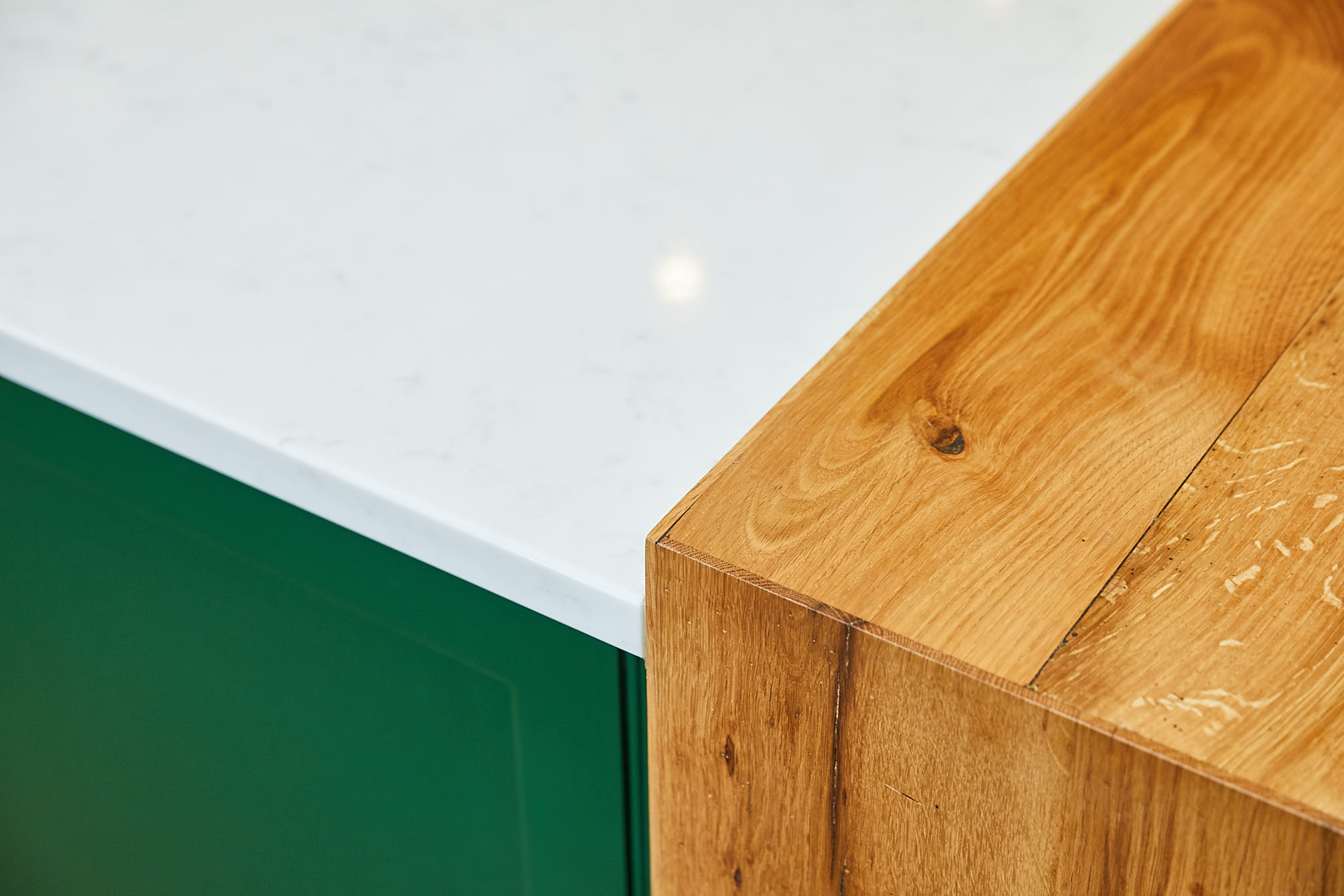 Oak breakfast bar against whitre quartz worktop and green painted kitchen cabinets