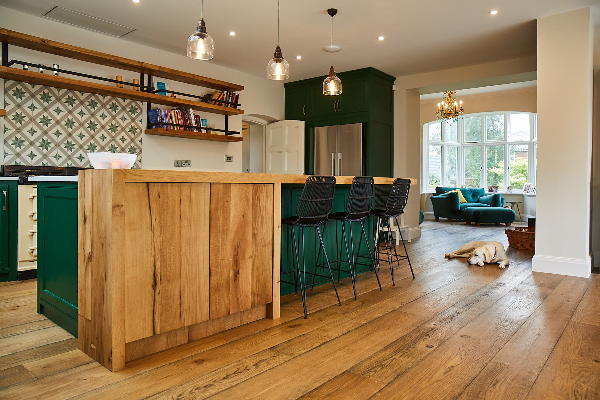 Dog sleeping in bespoke kitchen with green cabinets and oak breakfast bar