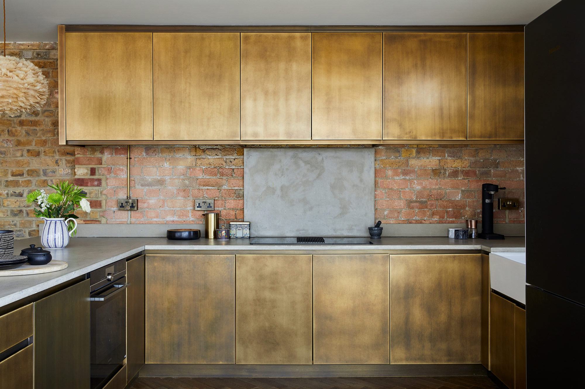 Aged brass kitchen with concrete worktops and exposed brick wall