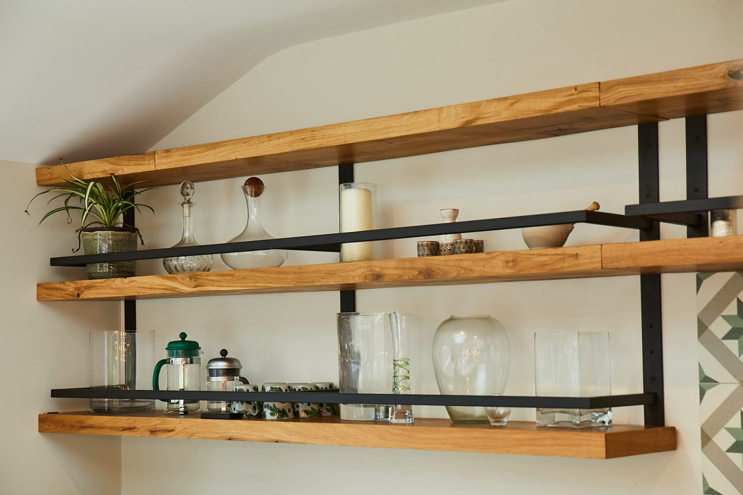 Open chunky oak shelves with glass vases and plants displayed