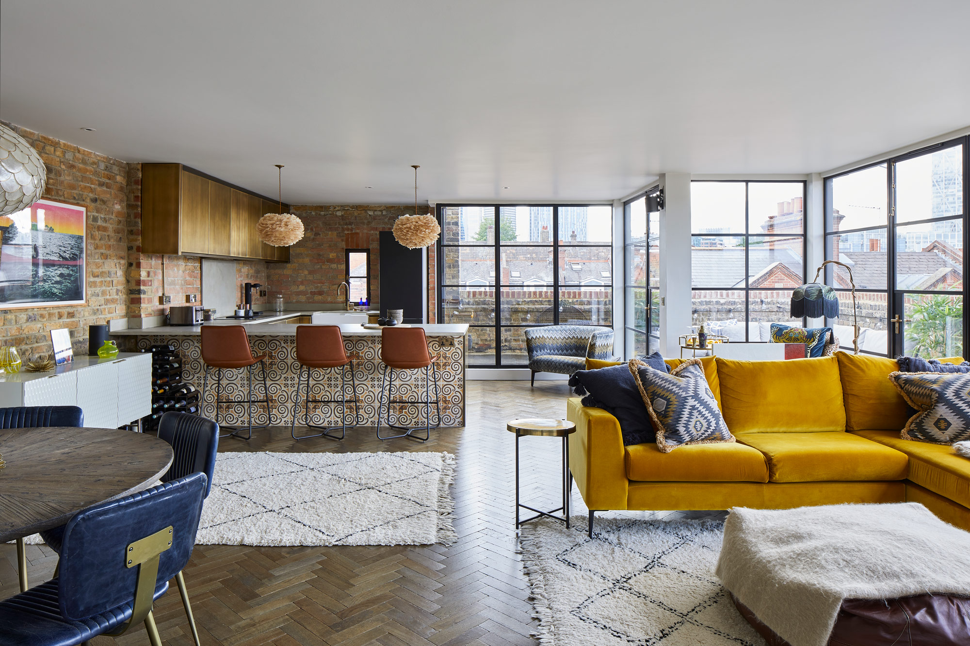Open plan London flat with yellow sofa and metal kitchen
