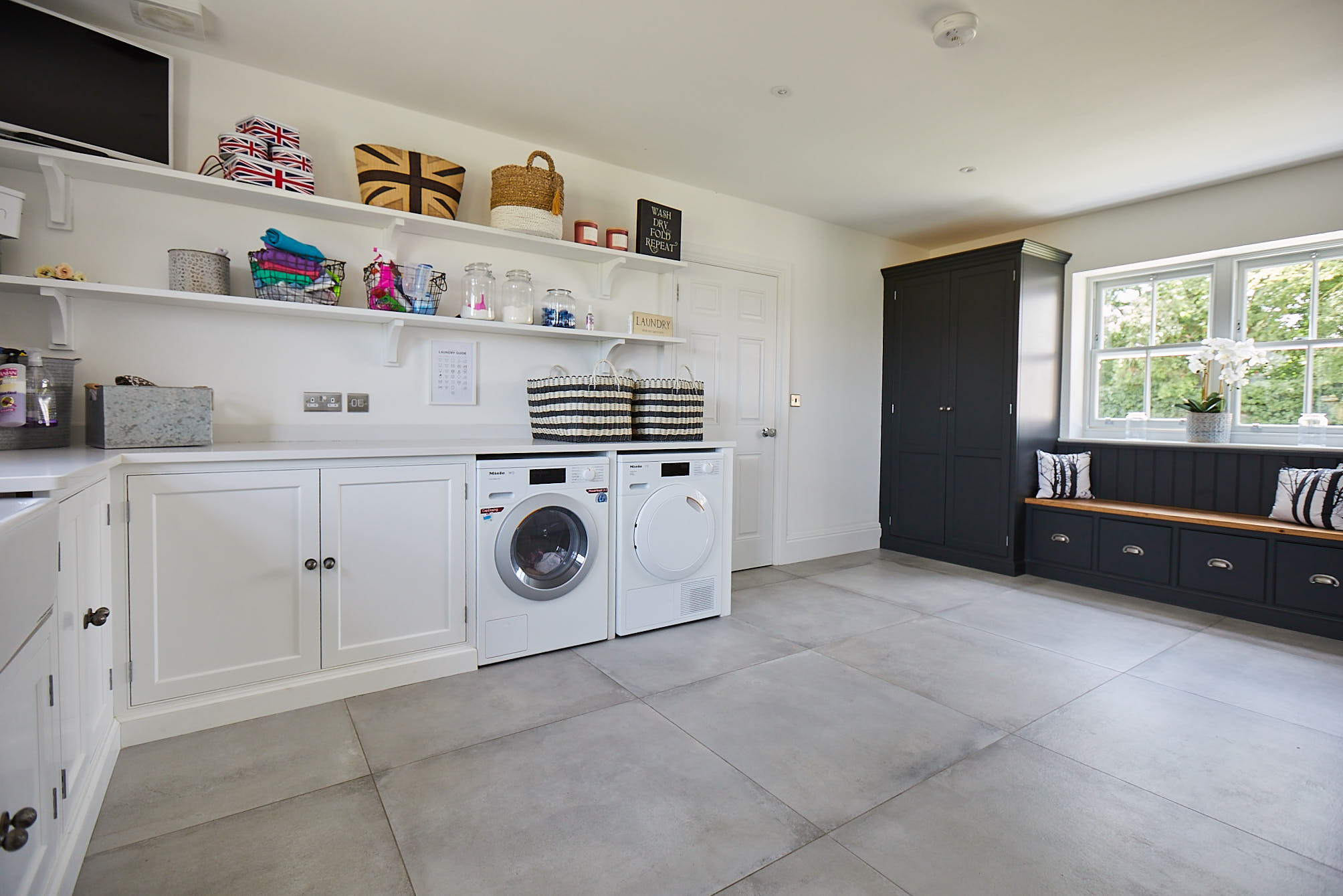 Contrasting white and black painted cabinets in utility room with freestanding washer and dryer