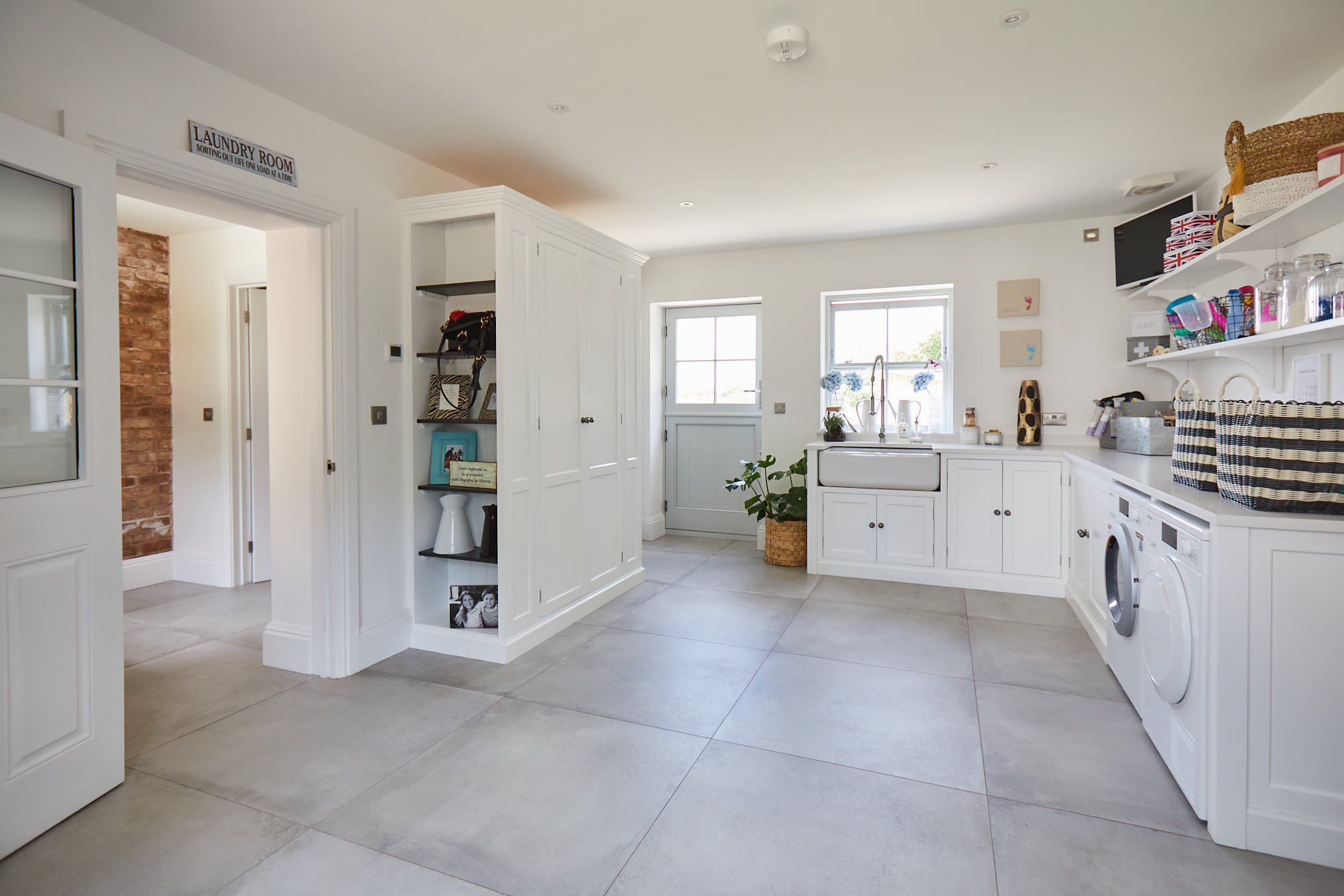 White utility room with open bookcase and Shaws double Belfast ceramic sink