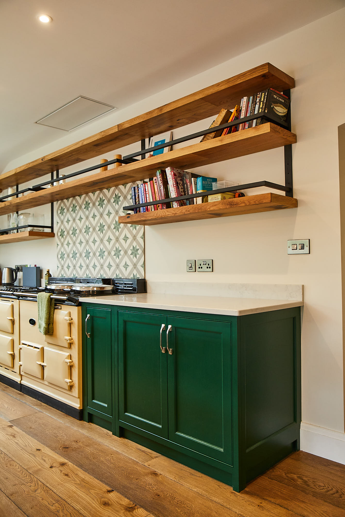 Chunky oak open shelves hang above green kitchen cabinets and cream AGA