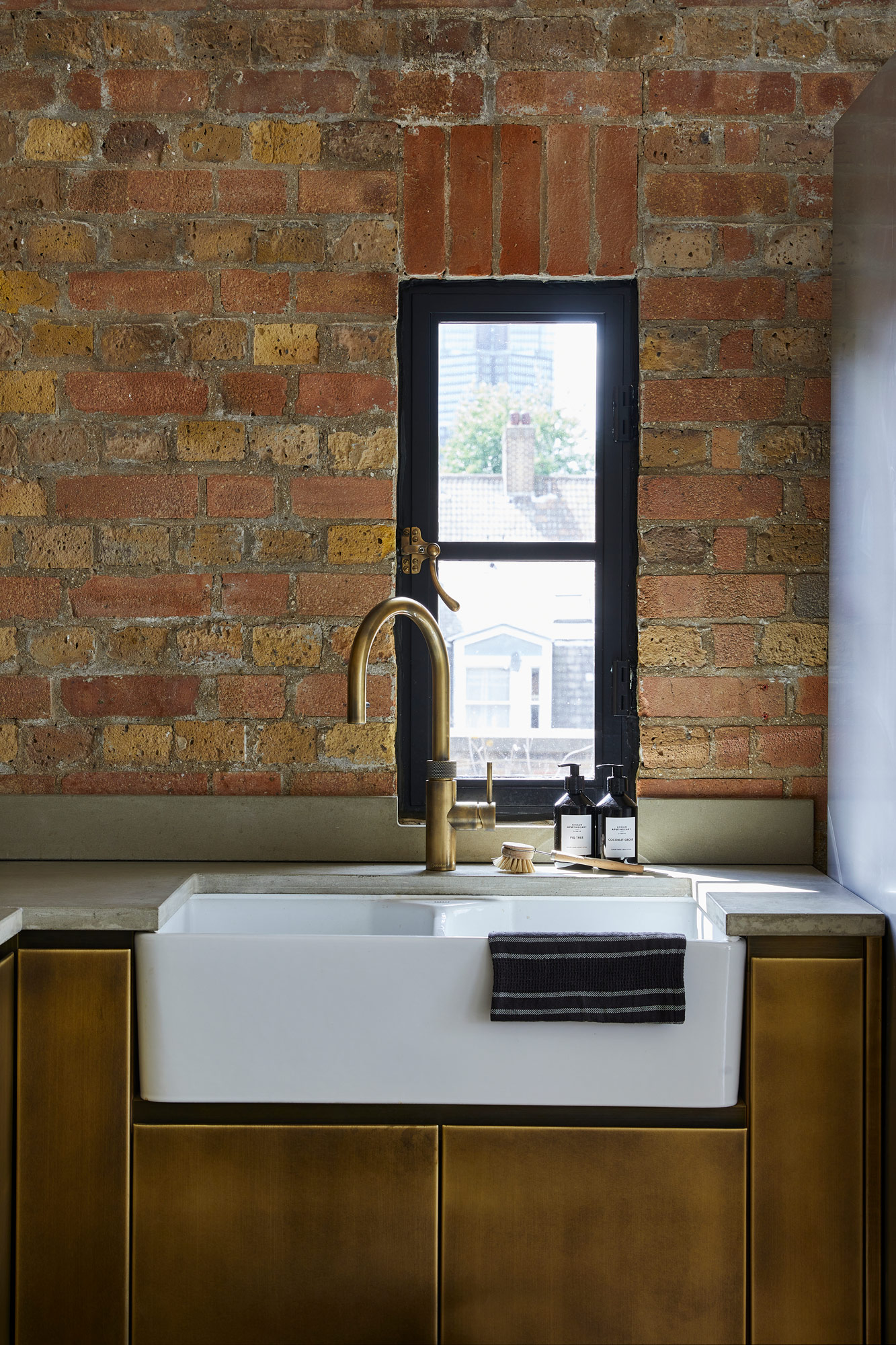 Ceramic belfast sink with concrete worktops and brass metal kitchen cabinets