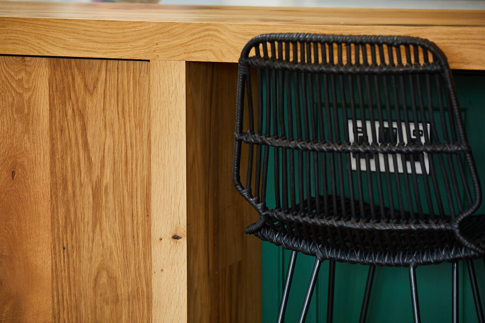 Black barstool backrest sits next to French oak kitchen cabinet