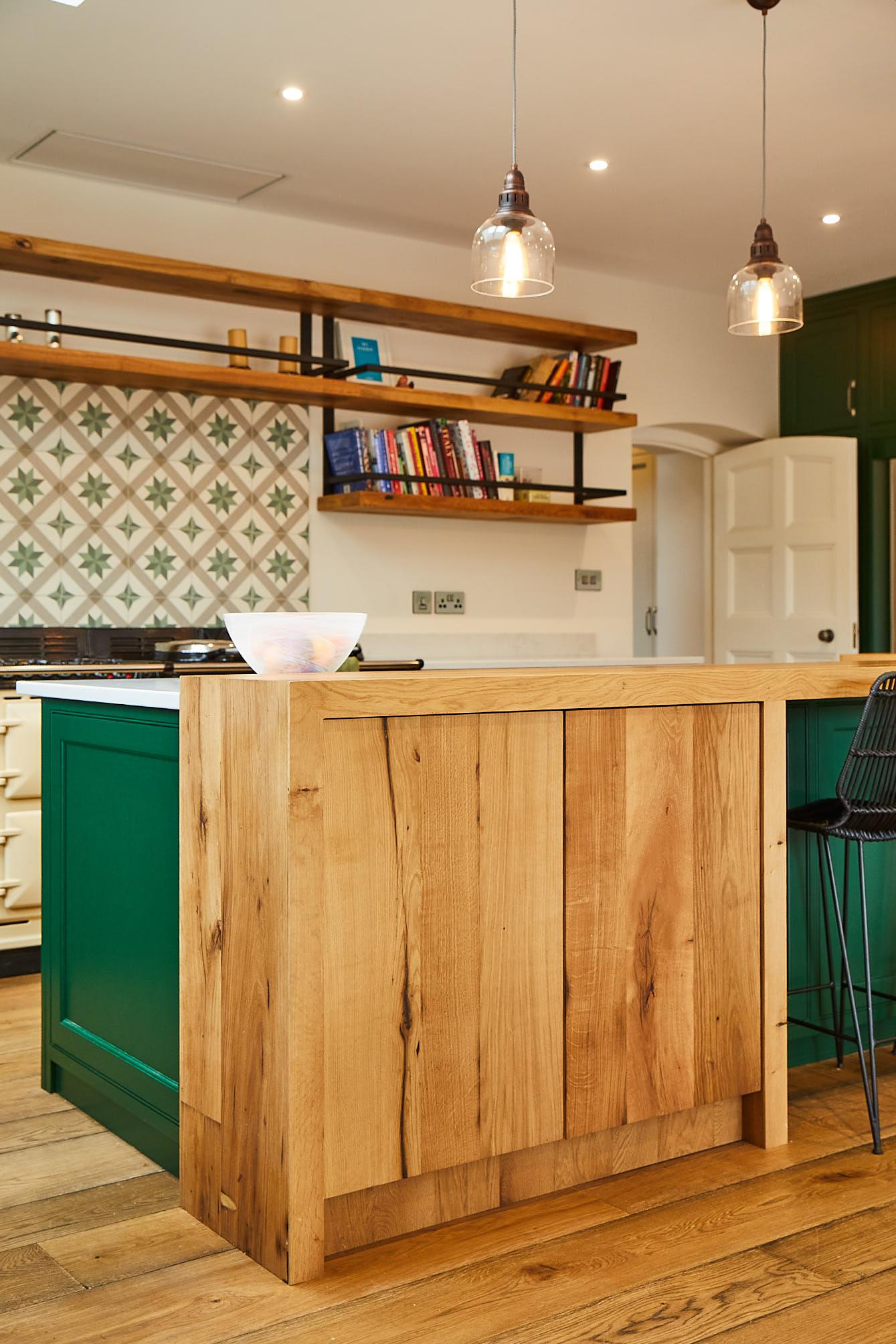 Clean oak wrap around breakfast bar with green kitchen cabinets