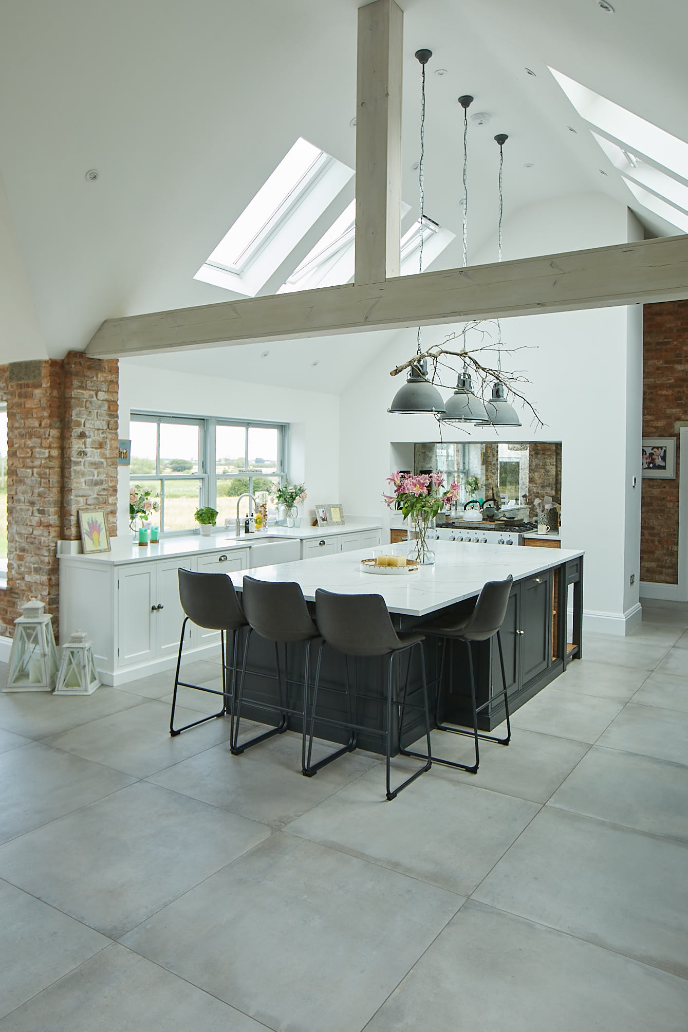 Large vaulted ceiling in open plan kitchen diner with white and black painted cabinets