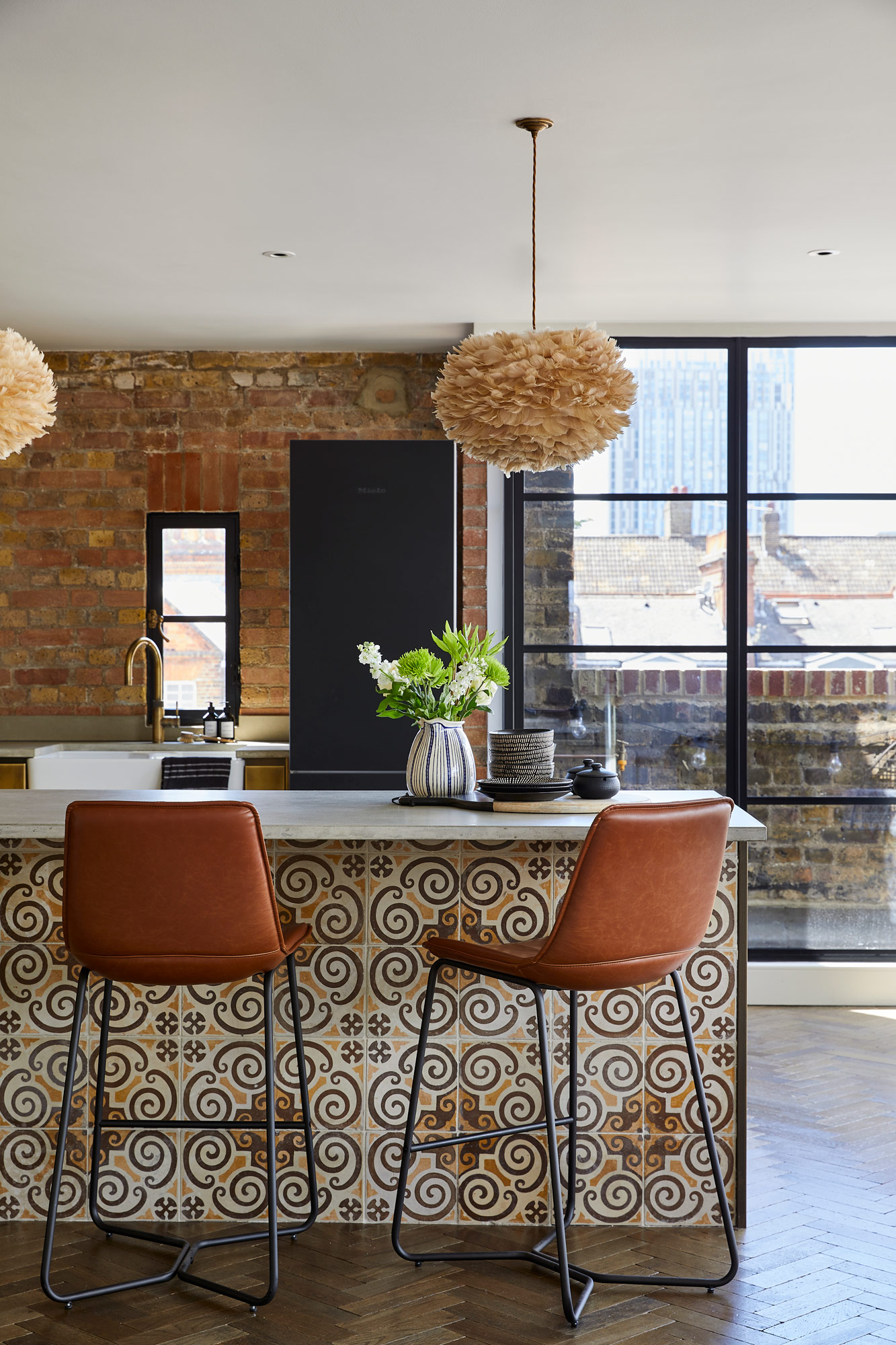 Brown leather barstools sit under metal kitchen with reclaimed tile kickboard