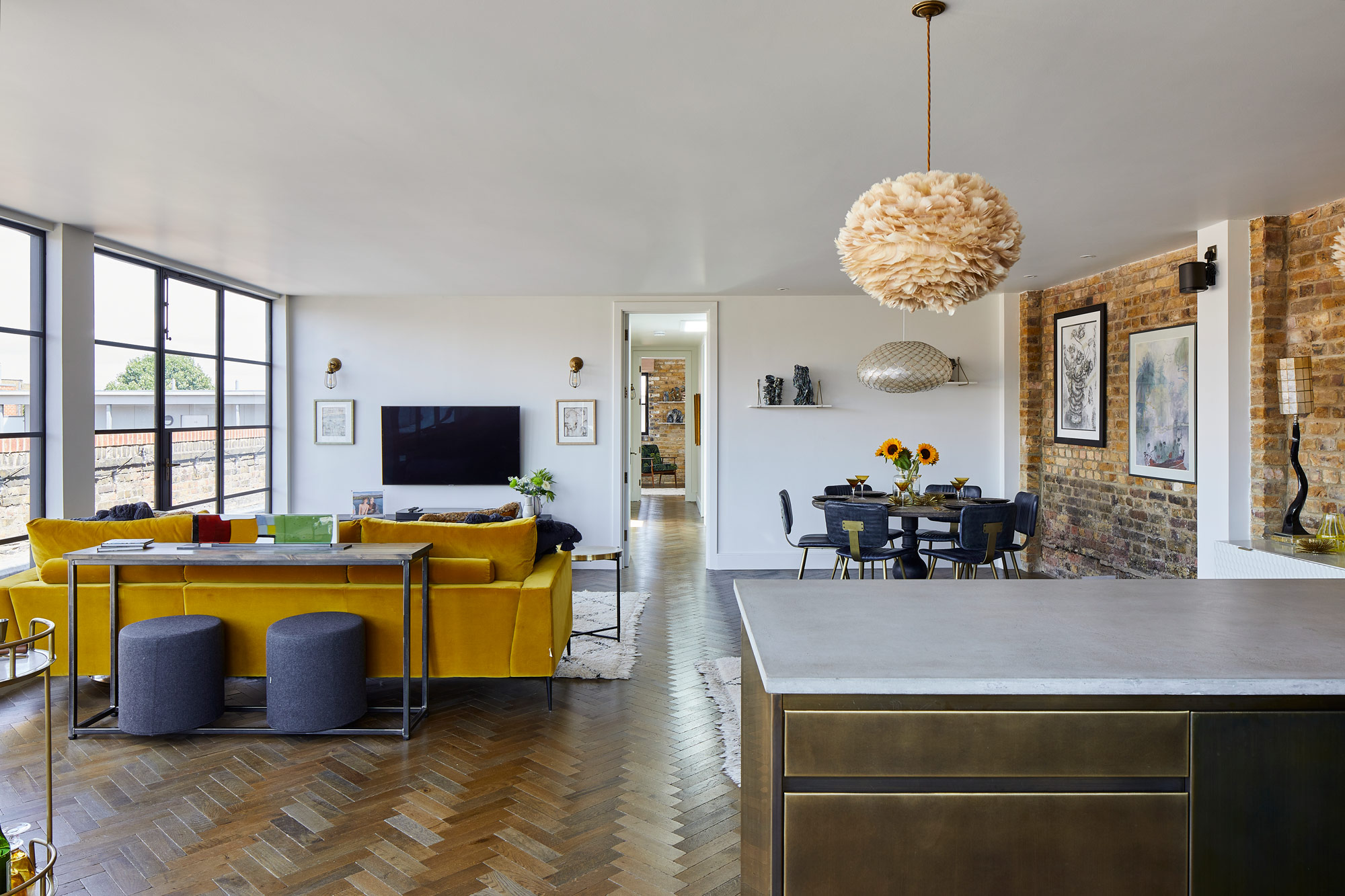 Open plan kitchen, living and dining area with metal kitchen and yellow sofa