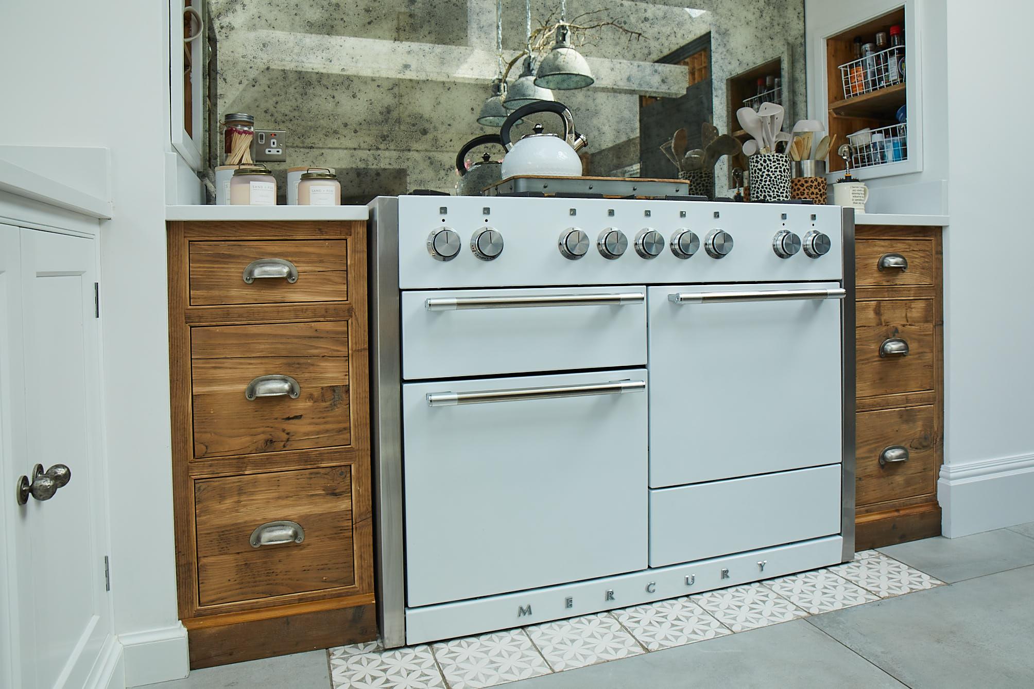 Rustic pan drawers beside white range cooker with antique mirror backsplash