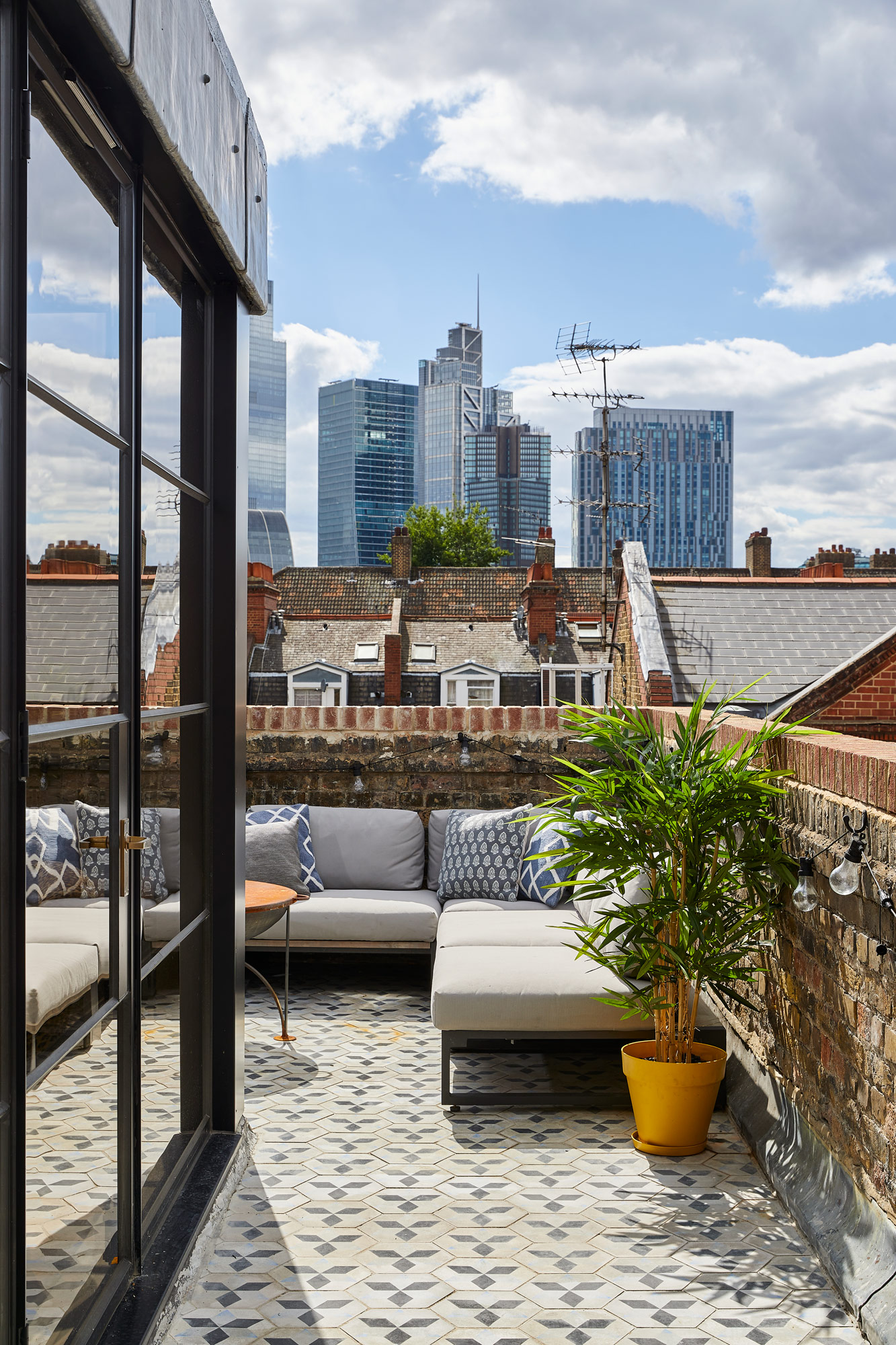 London rooftop apartment with upholstered outdoor furniture and reclaimed tiled patio