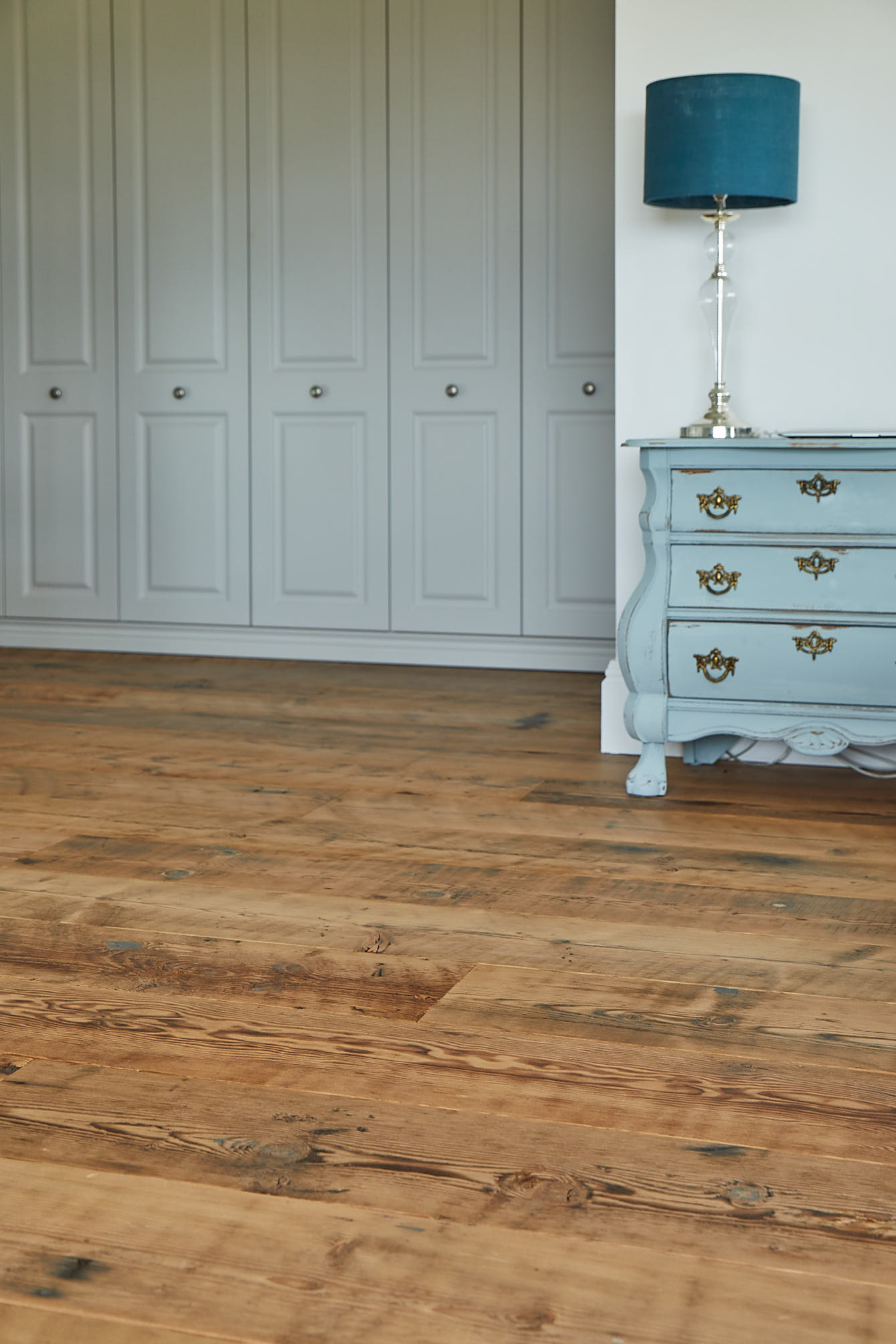 Original reclaimed flooring with blue bedside cabinet