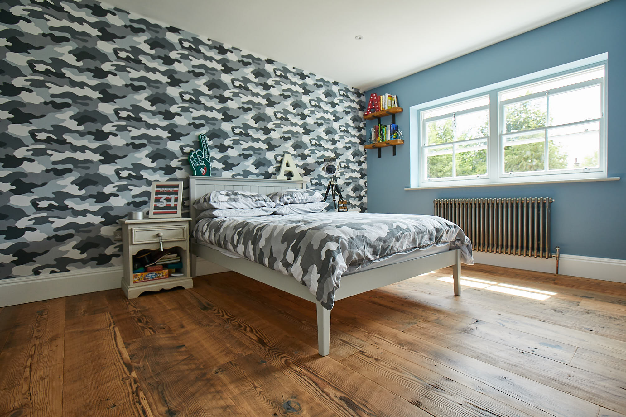 Camouflage wallpaper and rustic flooring in boys bedroom