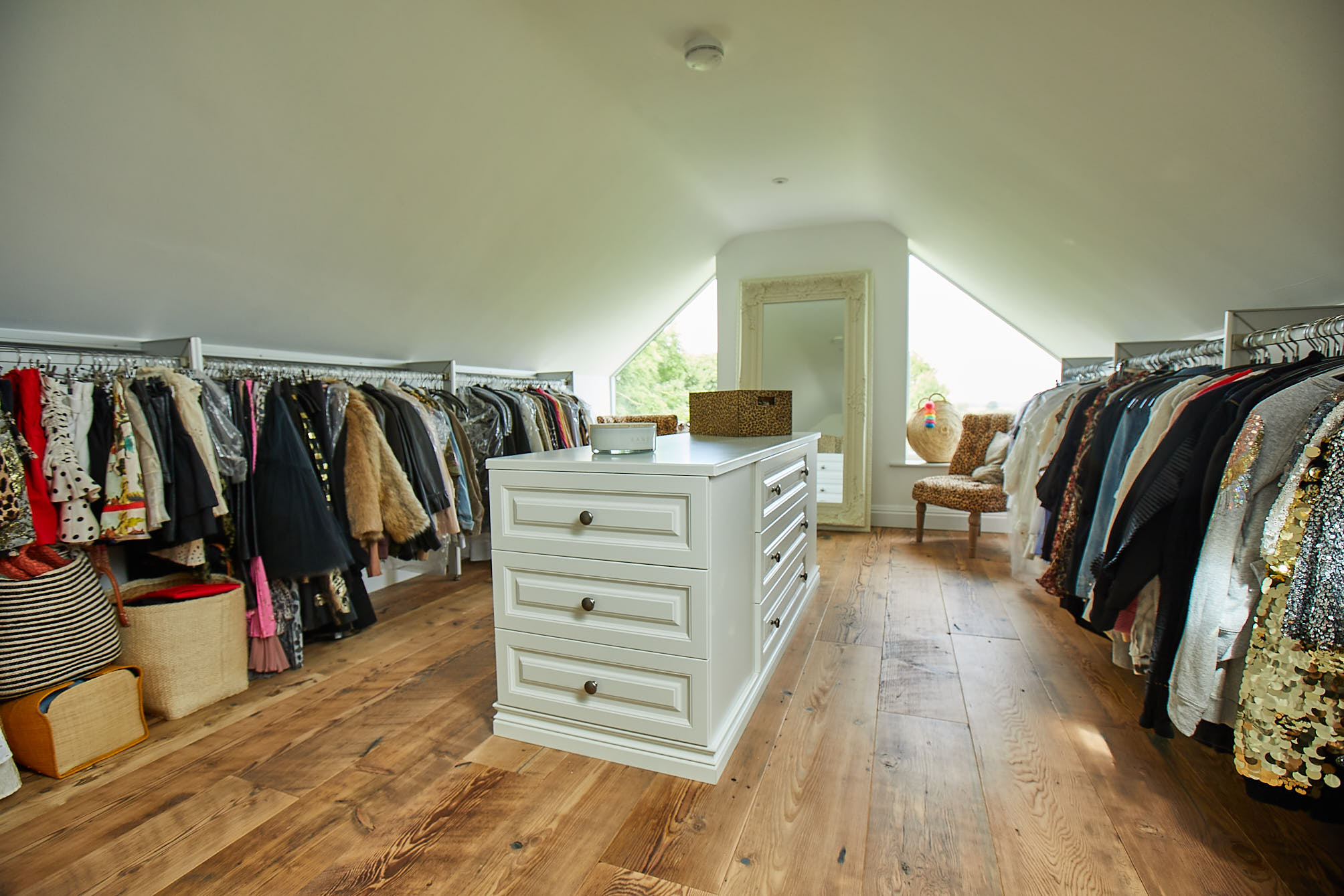 Walk in wardrobe with painted drawers and reclaimed flooring