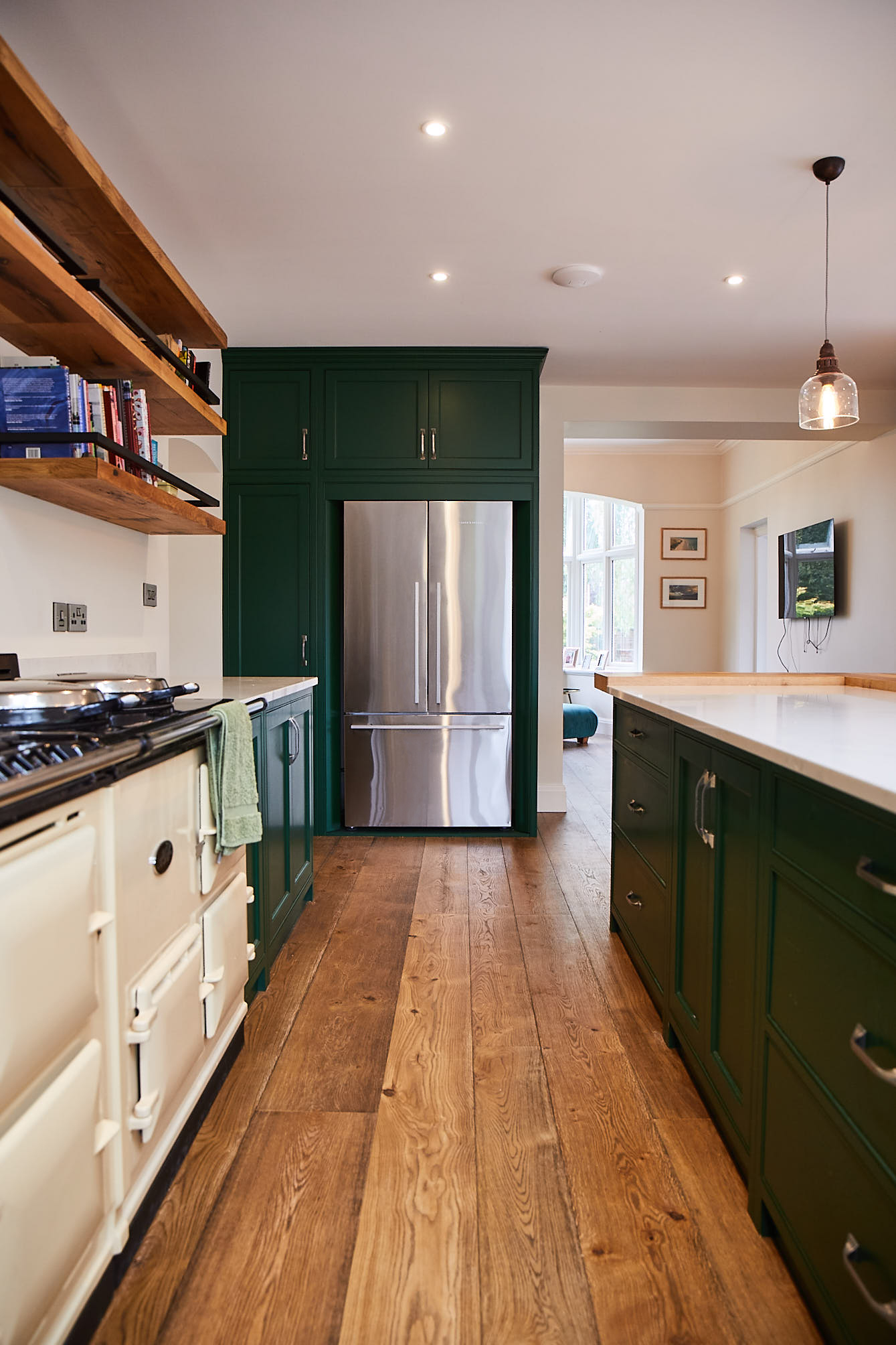 Stainless steel Fisher Paykel frindge freezer with green painted kitchen cabinets and oak flooring