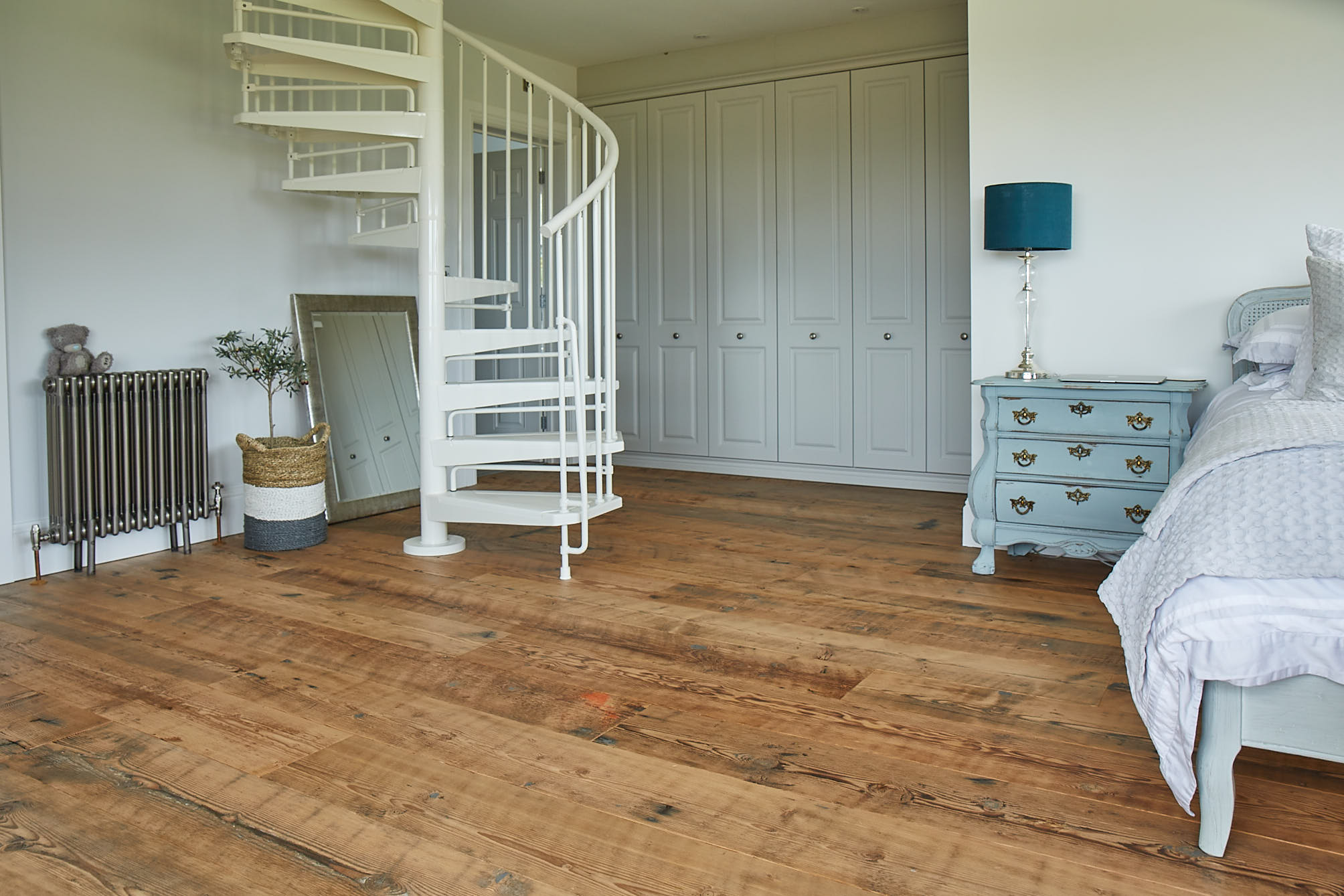 Rustic flooring contrasts with white fitted wardrobes and spiral staircase in bedroom