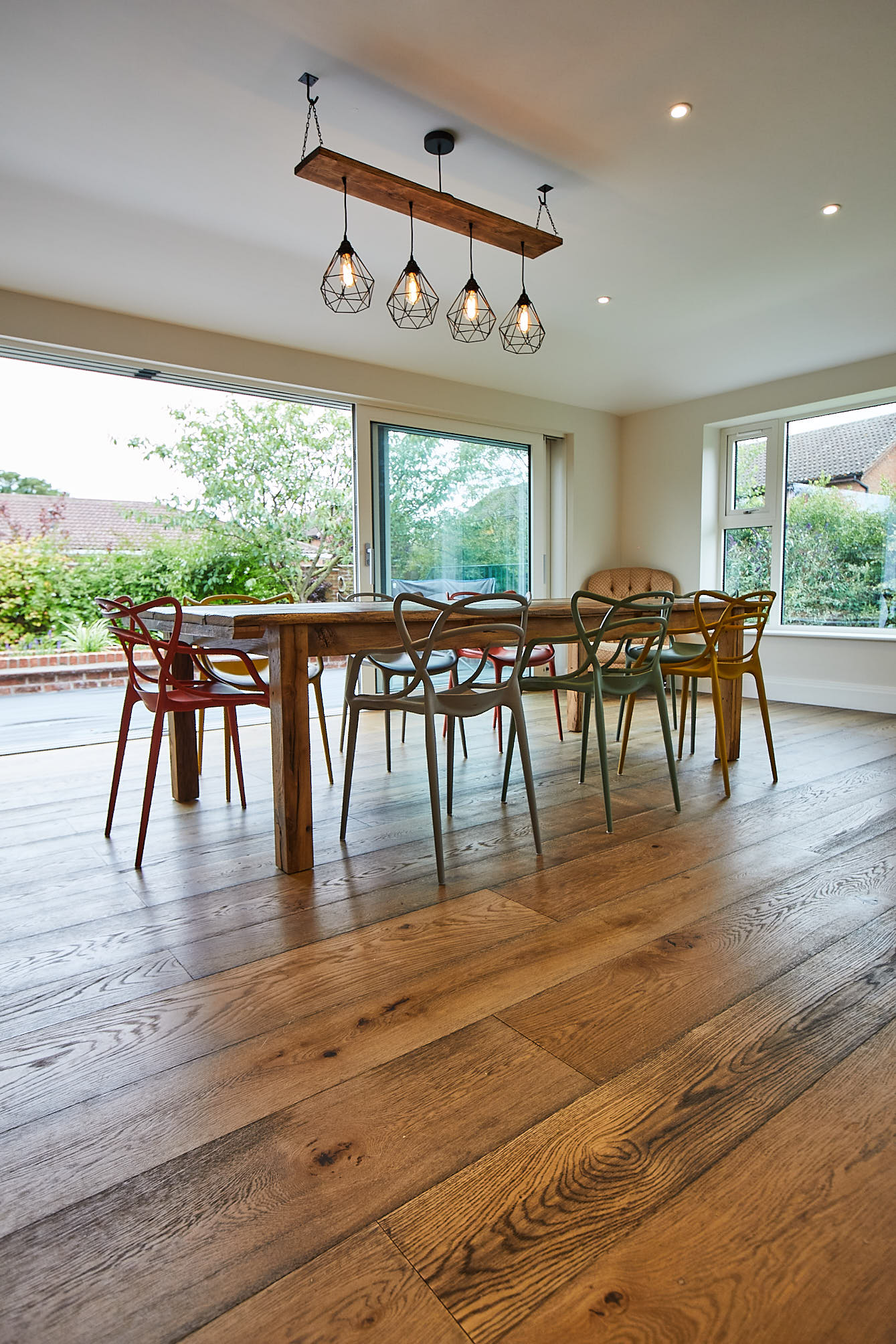 Reclaimed oak dining table sits on oak flooring