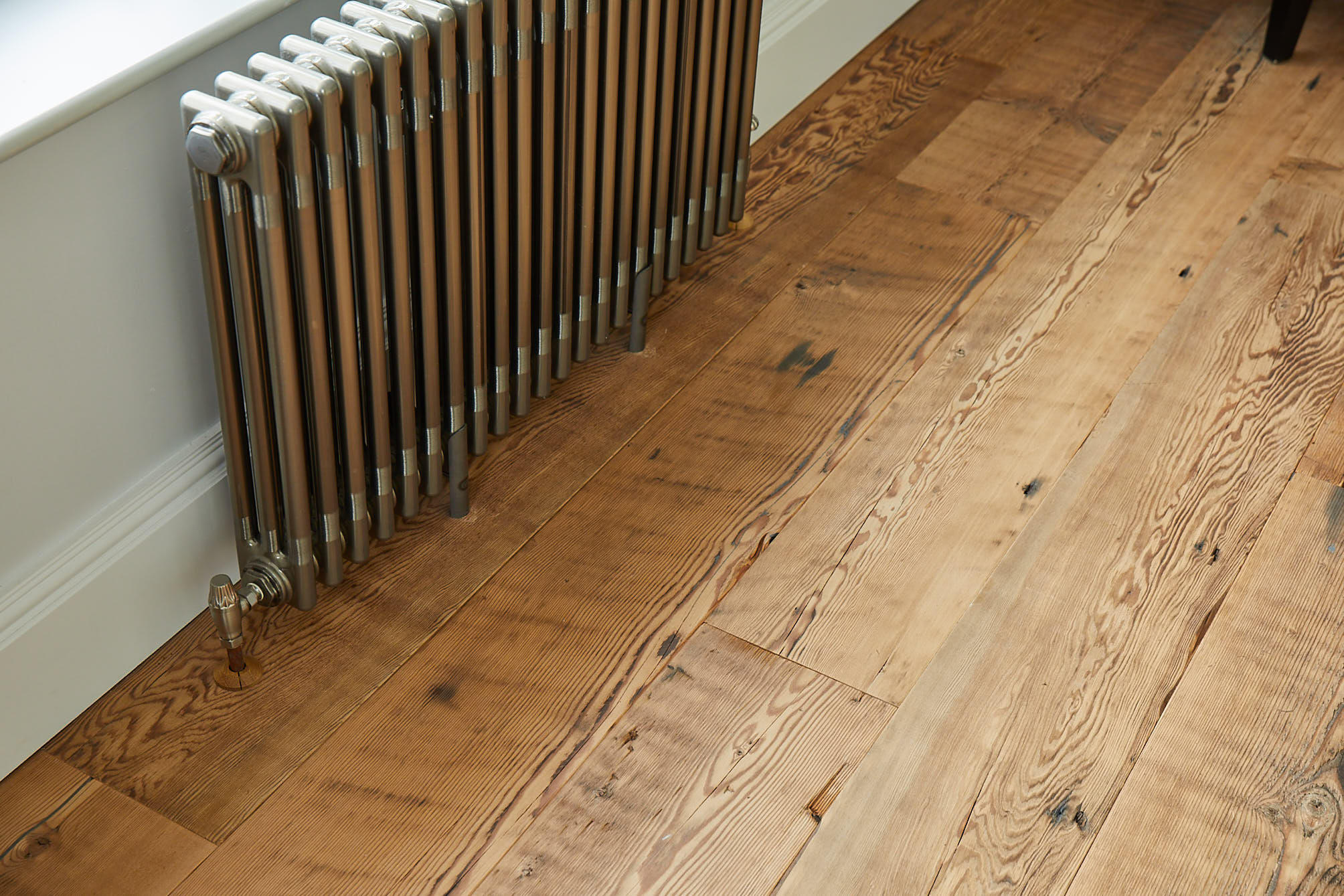 Cast iron radiator sits on reclaimed flooring
