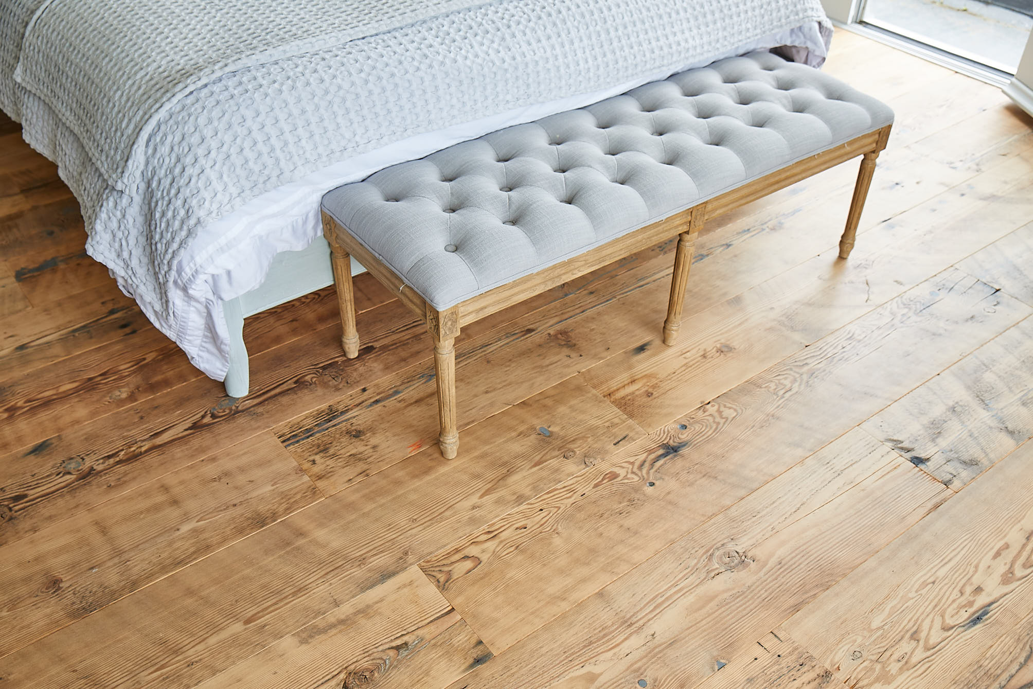 Upholstered seat on reclaimed rustic flooring by The Main Company