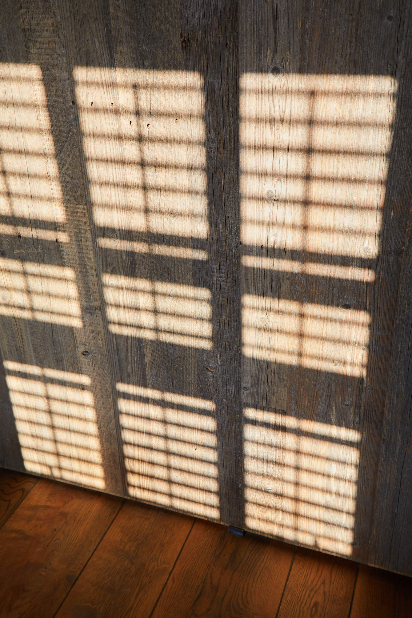 Sunlight hitting reclaimed wood cladding
