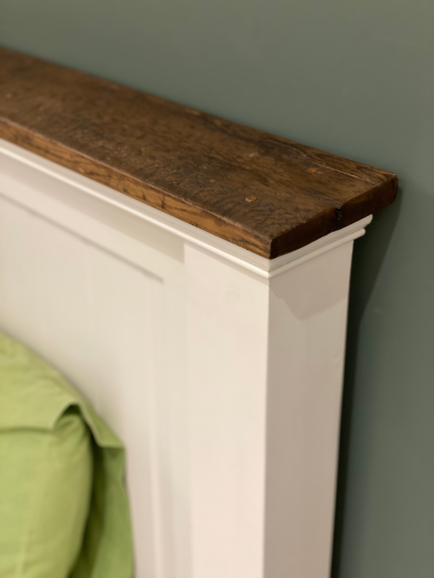 Painted bed headboard with rustic wood capping