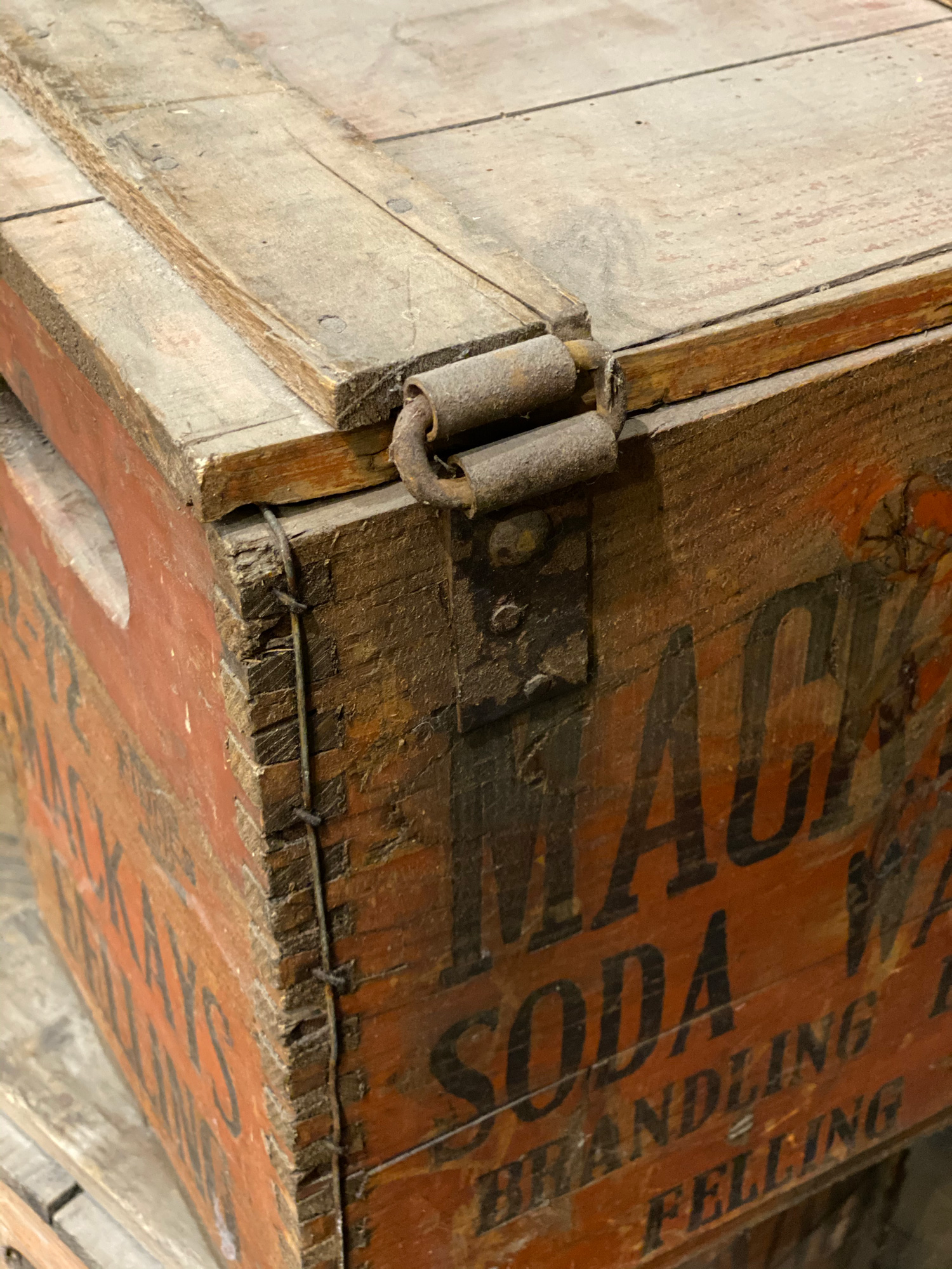 Rusty hinge on reclaimed soda box crate