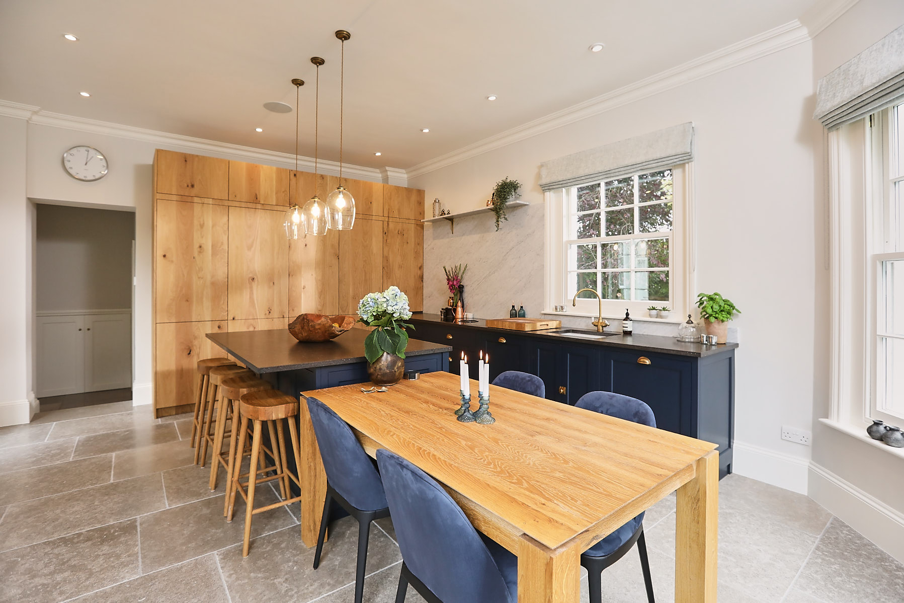 Bespoke blue kitchen with tall French oak cabinets and oak dining table