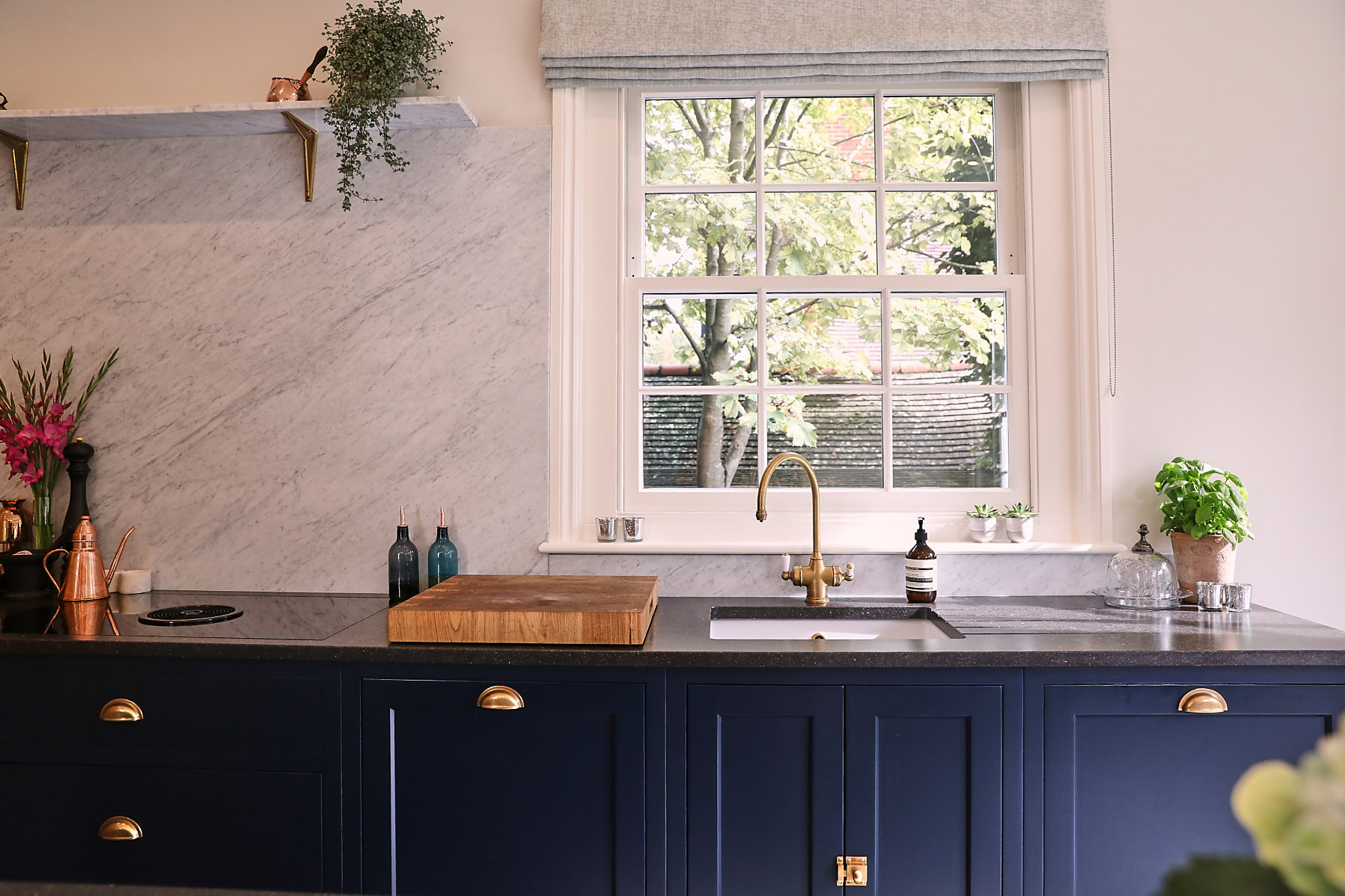 Painted blue kitchen with BORA downdraft and antique brass tap
