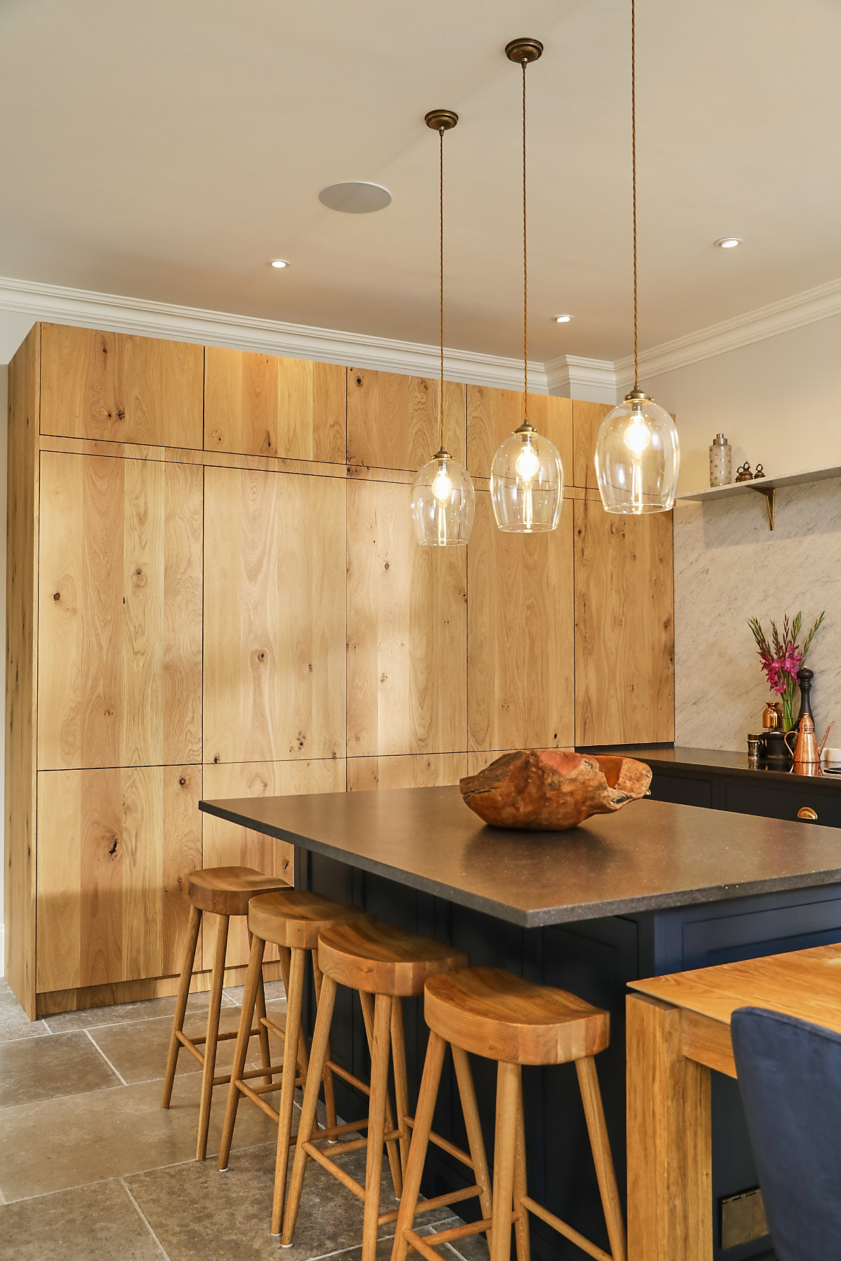 Glass pendant lights above kitchen island and oak farmhouse breakfast bar stools