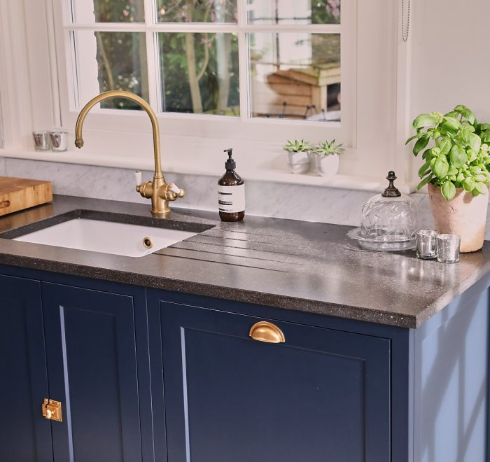 Integrated dishwasher with painted blue in-frame cabinets with antique copper cup handle