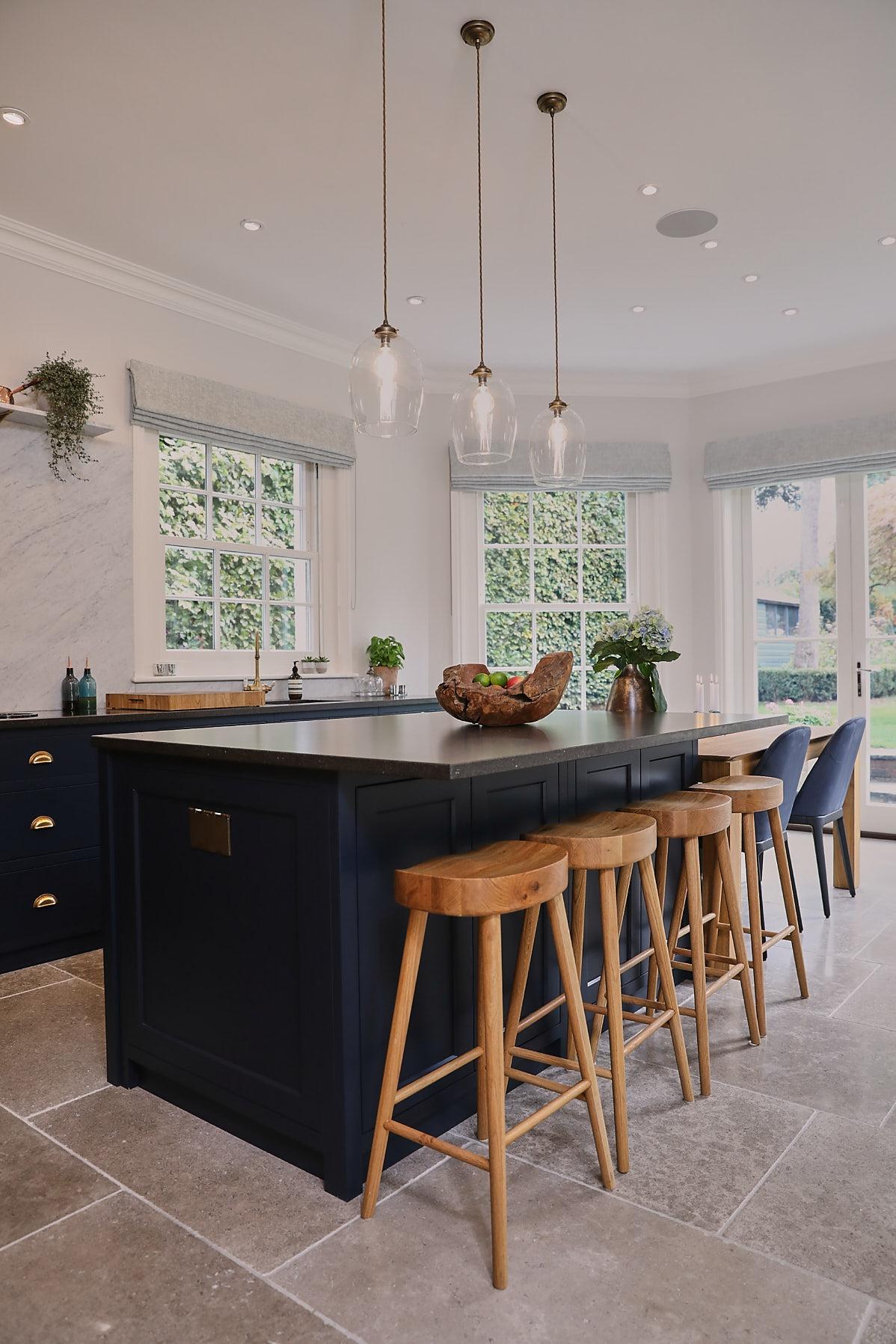 Blue kitchen island with oak barstools