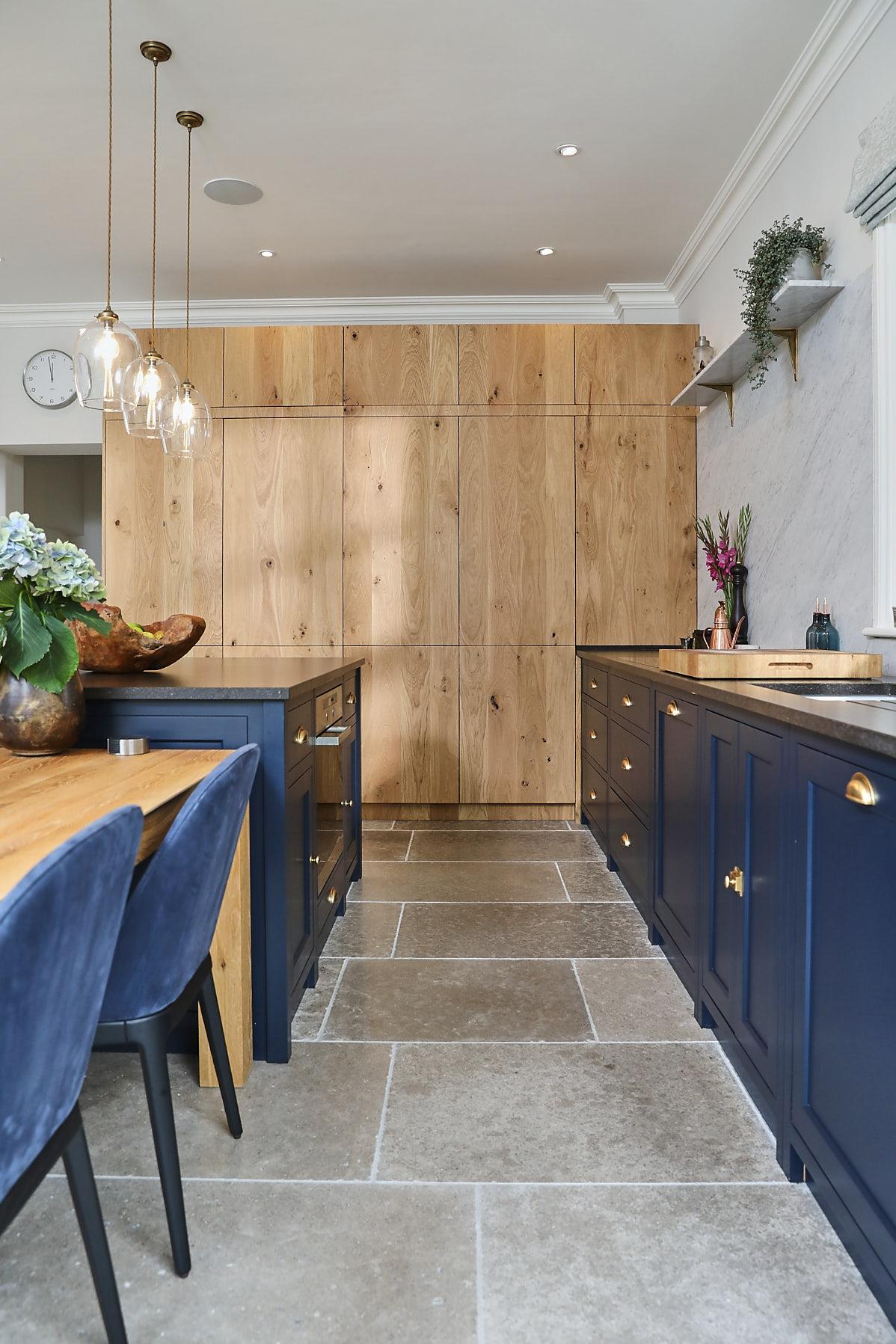 Tall bespoke oak cabinets in blue kitchen