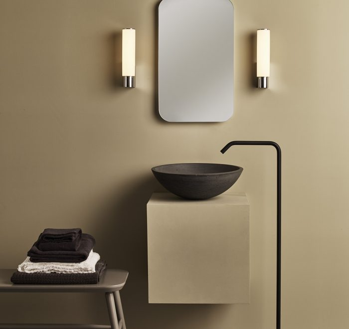 Round solid concrete basin sink in a black finish with grey bathroom