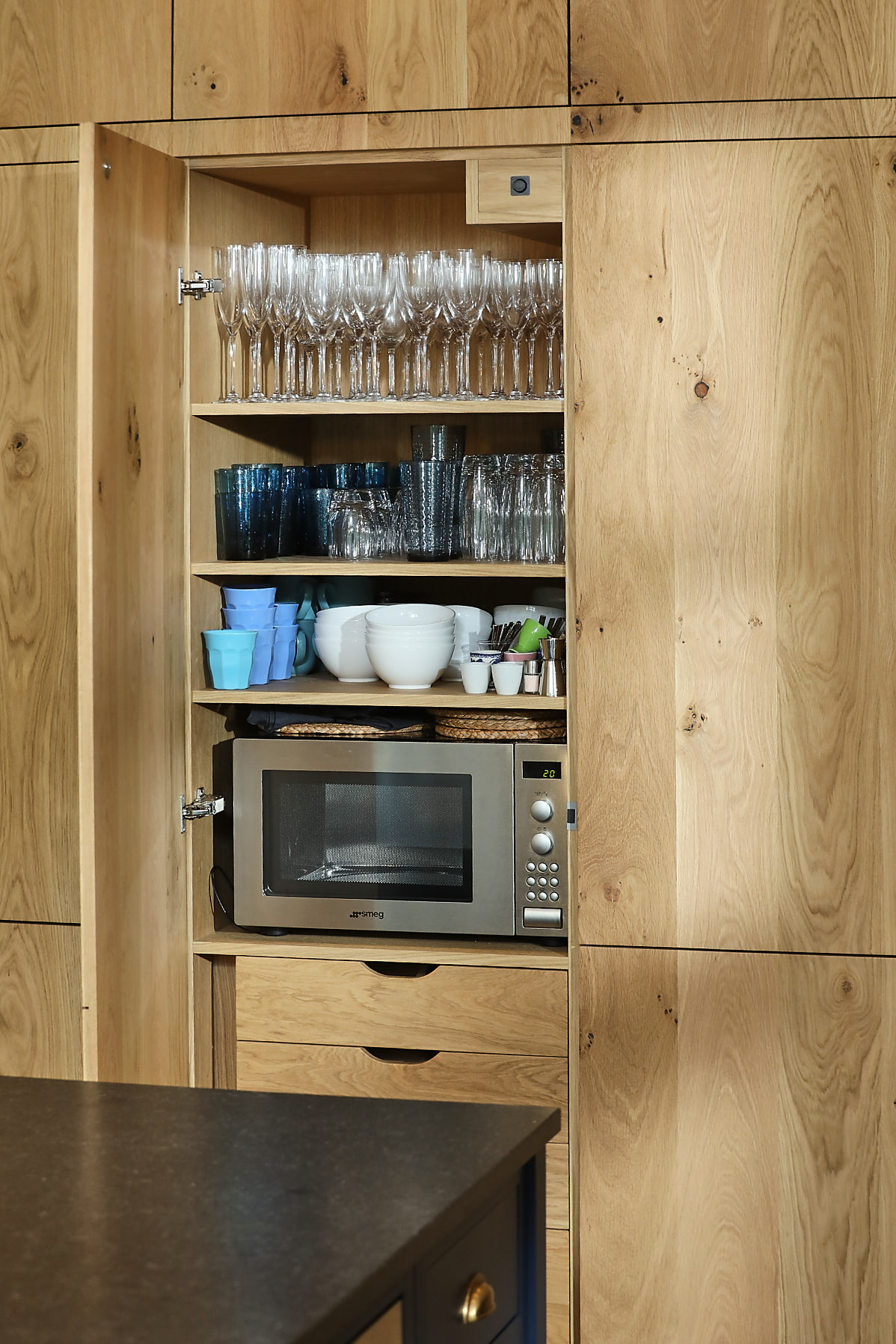 Glasses and microwave stored in tall oak kitchen cabinets