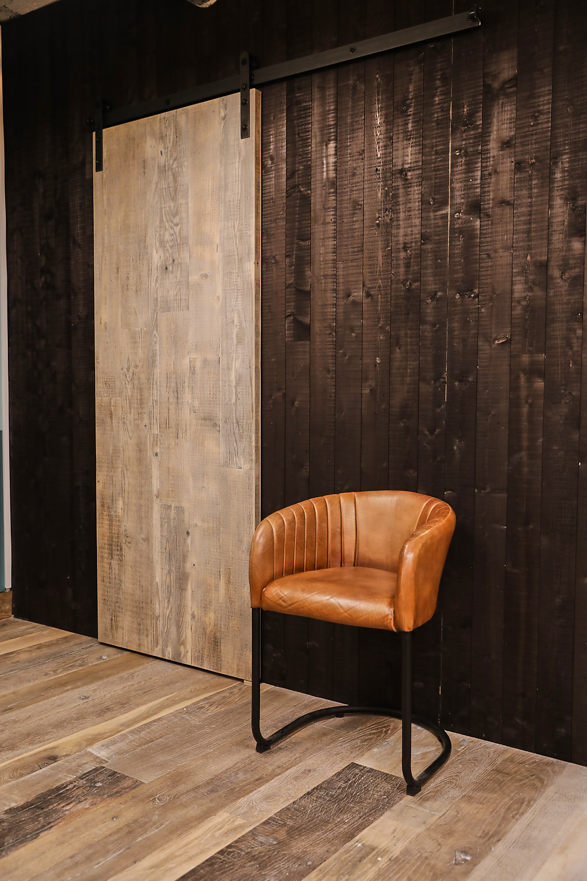 reclaimed whitewash sliding barn door against dark black wall cladding