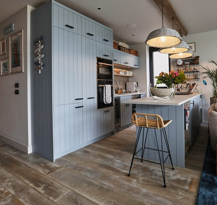 Baby blue bespoke kitchen with wooden flooring