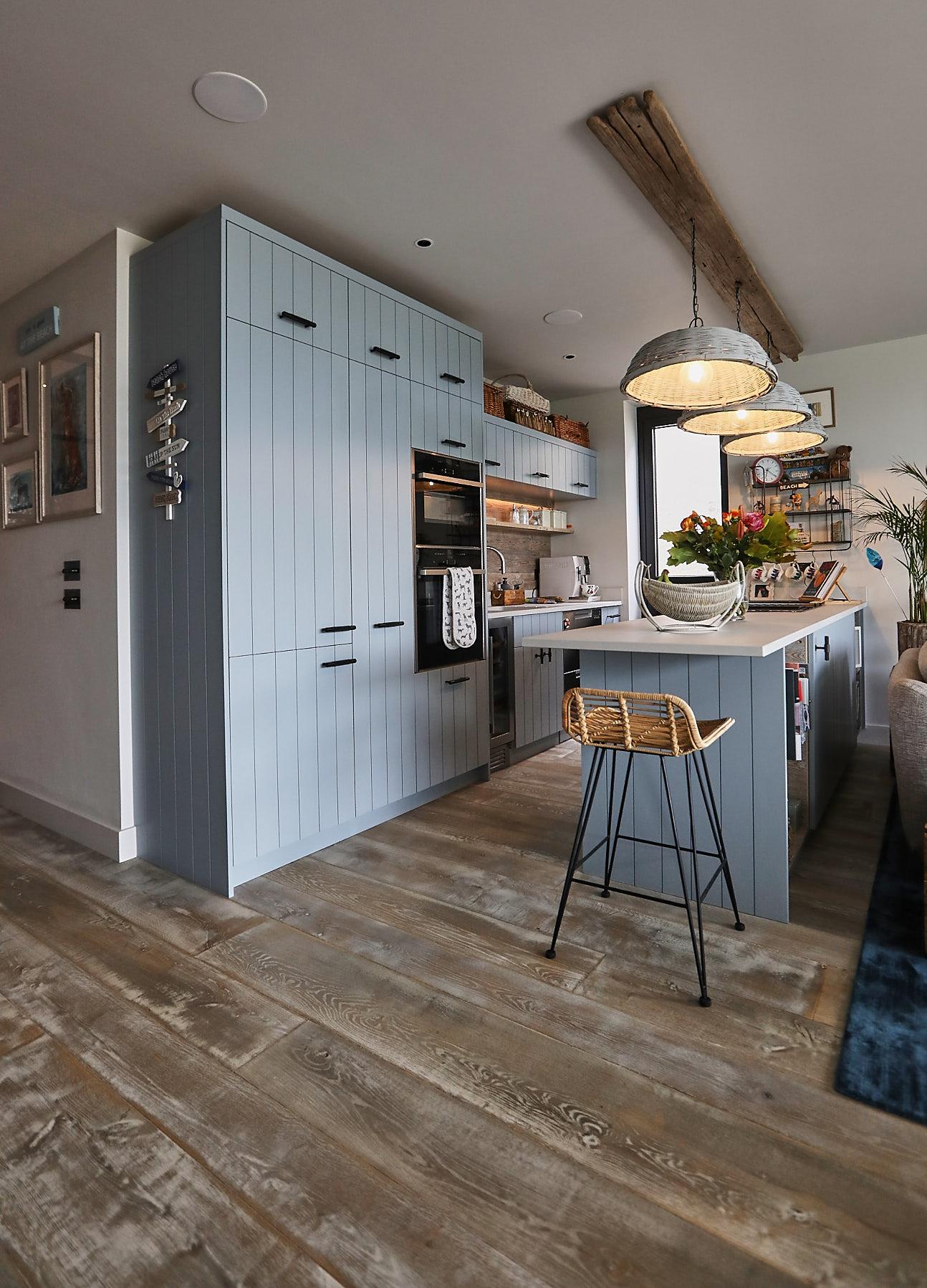 Baby blue bespoke kitchen with wooden flooring